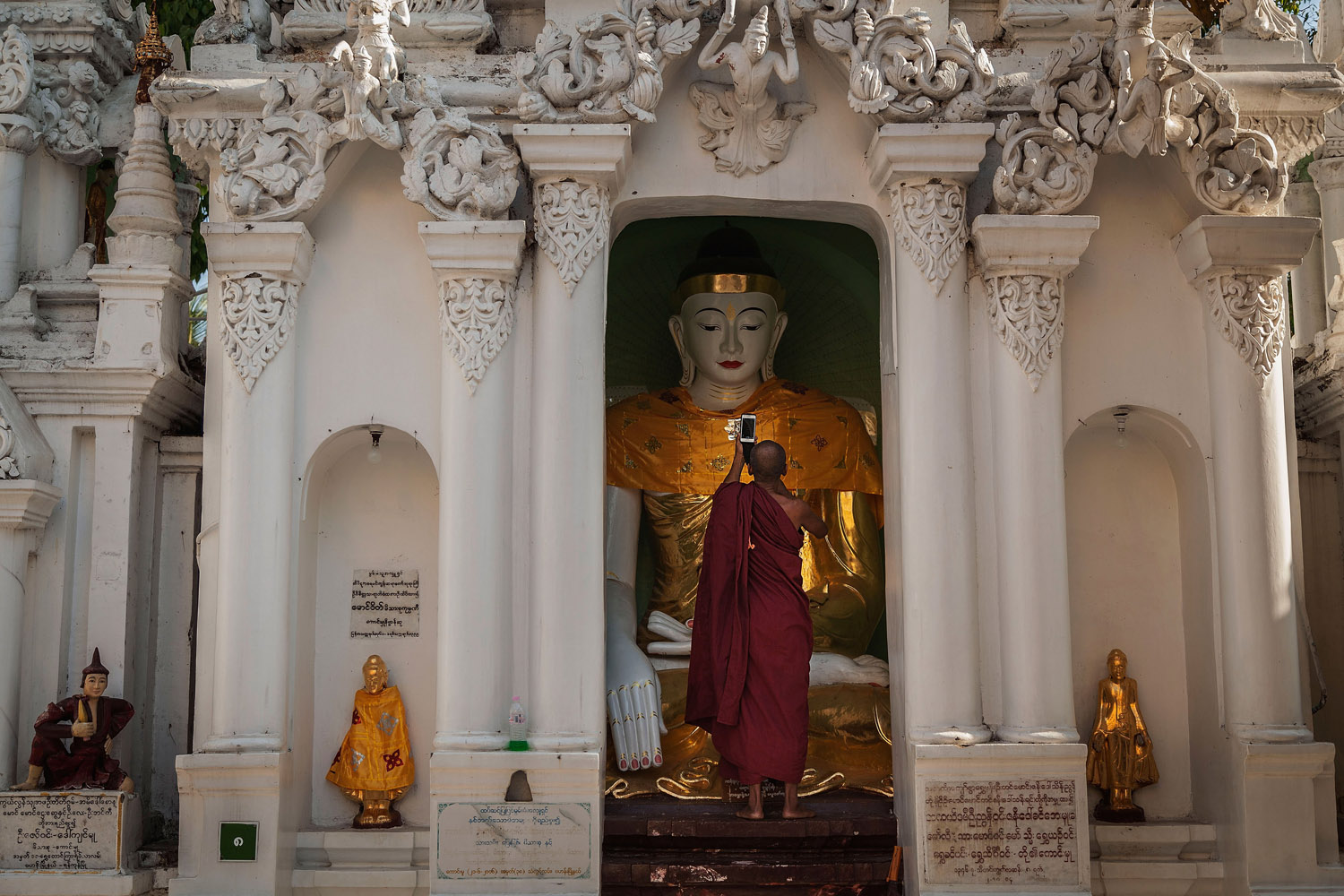 Mar. 15, 2014.  A Burmese monk takes a photo with his cell phone during the Shwedagon Pagoda festival in Yangon, Burma. The festival is celebrated by thousands of devout Buddhists in the country.