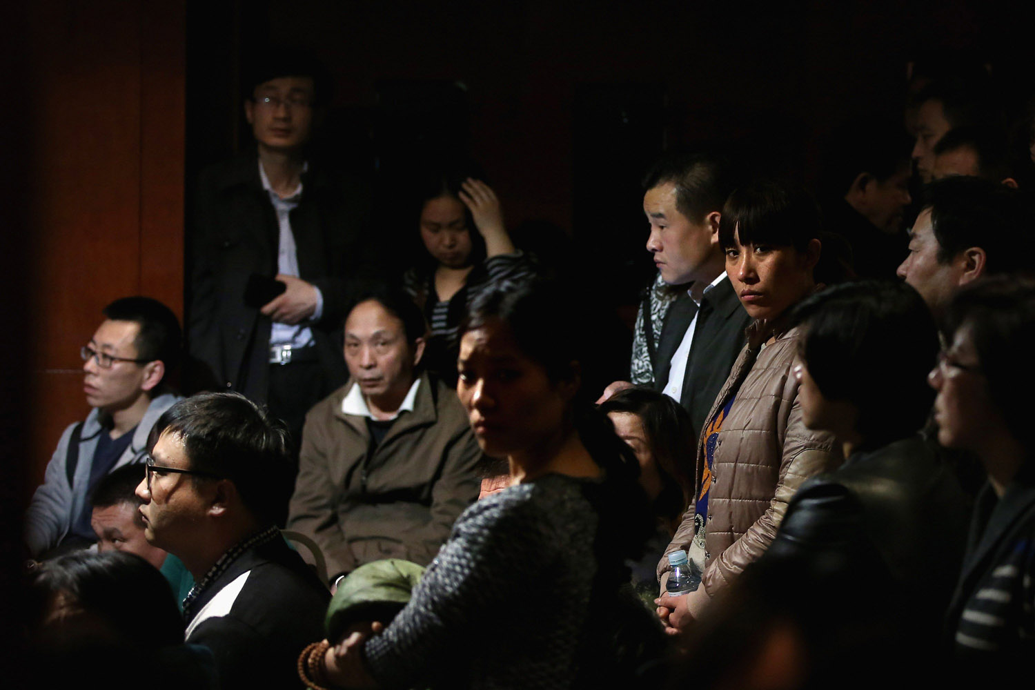Mar. 17, 2014. Chinese relatives of the missing passengers who were travelling onboard Malaysia Airlines flight MH370 watch a television displaying a Malaysian press conference at Lido Hotel in Beijing, China. All passengers and crew are currently under investigation and 22 countries are involved in the search.