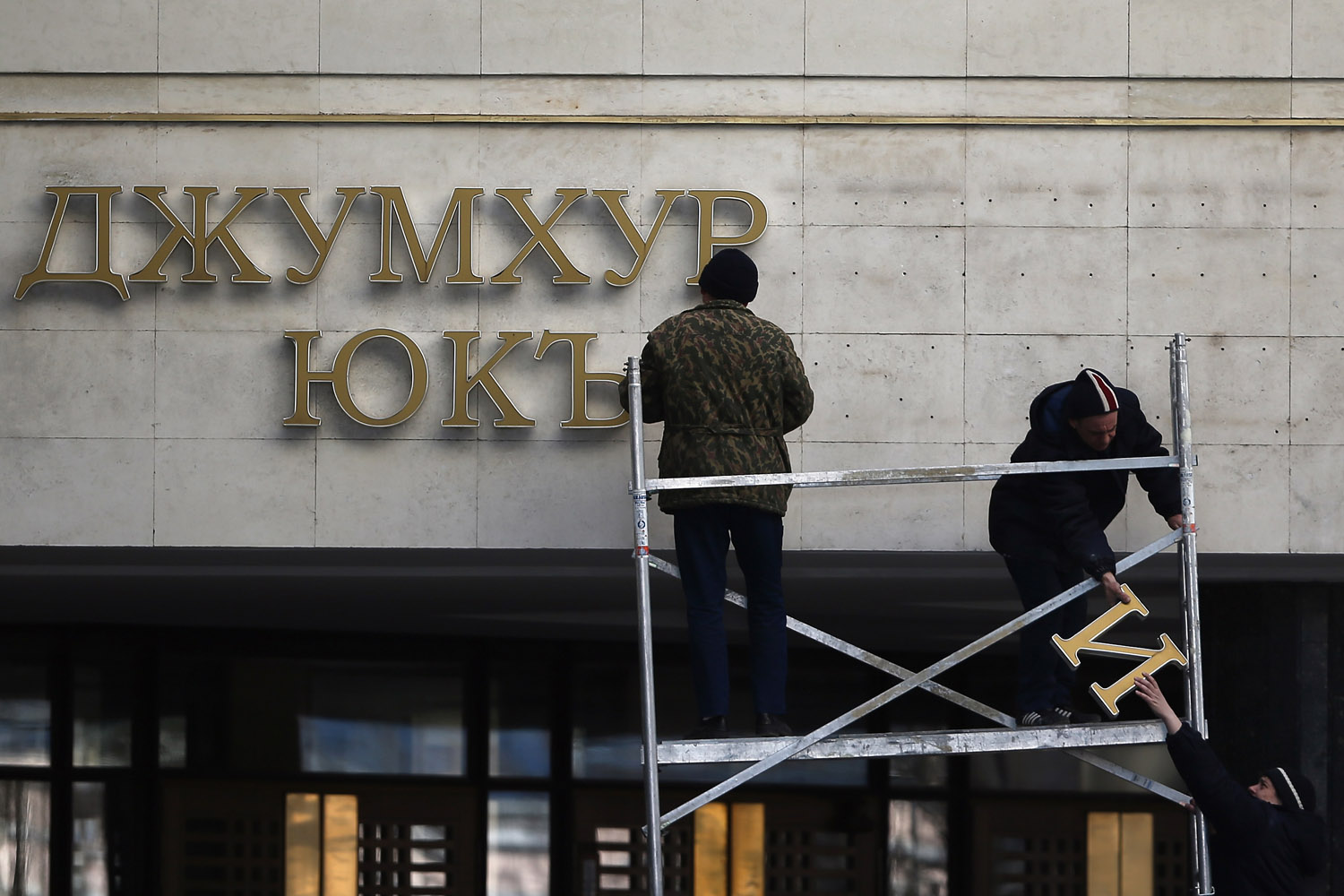 Mar. 18, 2014.   Workmen change the lettering on the Parliament building to a sign that reads 'Crimean Autonomous Council' in Simferopol, Ukraine.   Voters on the autonomous Ukrainian peninsular of Crimea voted overwhelmingly to secede from their country and join Russia.