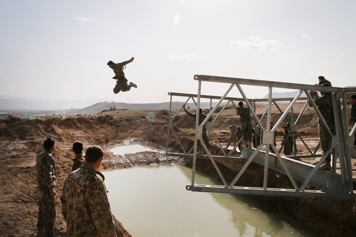 Mar. 18, 2014.  A soldier with the Afghan National Army's (ANA) National Engineer Brigade leaps from the top of a Mabey-Johnson portable pre-fabricated bridge which his unit was learning to construct.