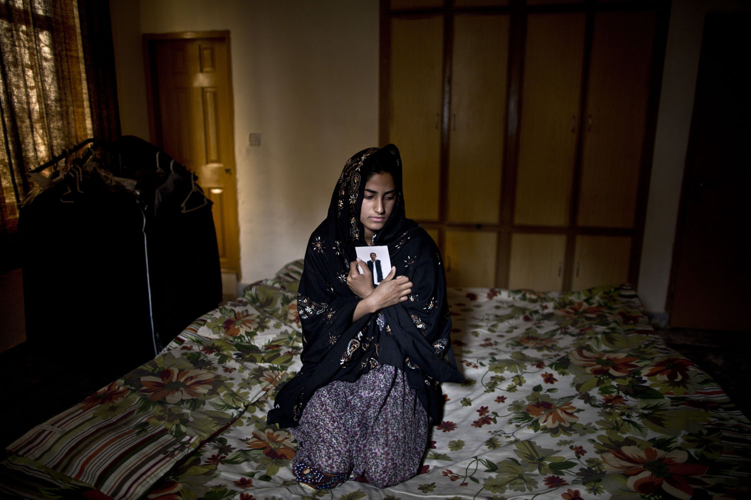 Mar. 16, 2014. Pakistani Syeda Aima Tanveer, 20, daughter of lawyer Tanveer Haider, 58, who was one of eleven victims that was killed by suicide bombers in an attack on a court complex on March, 3 2014, sits on her father's bed embracing his photograph, at their home on the outskirts of Islamabad, Pakistan.