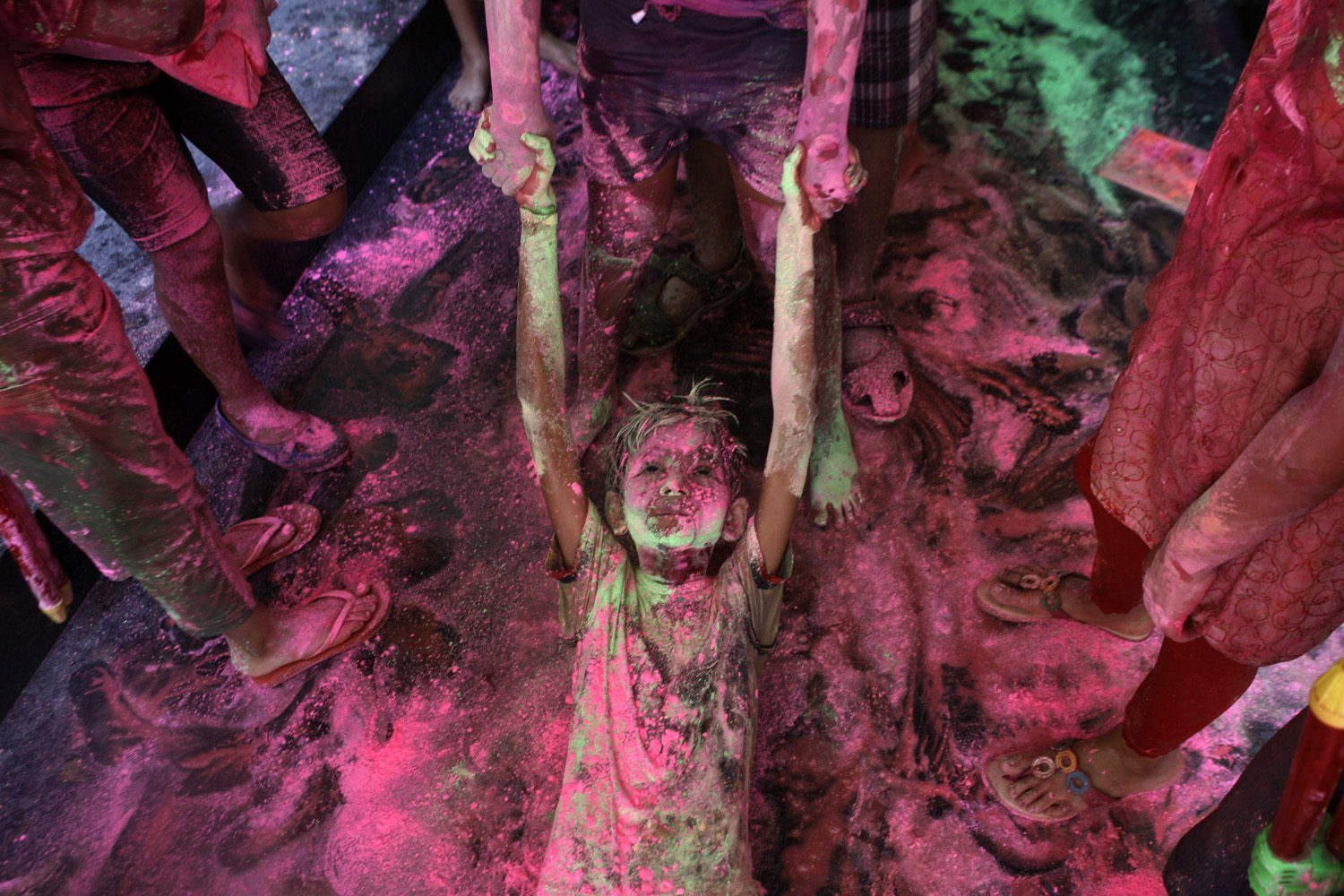 Mar. 16, 2014. An Indian boy drags another on the floor of an apartment as they play with colored powder during the Holi festival in Chennai, India.
