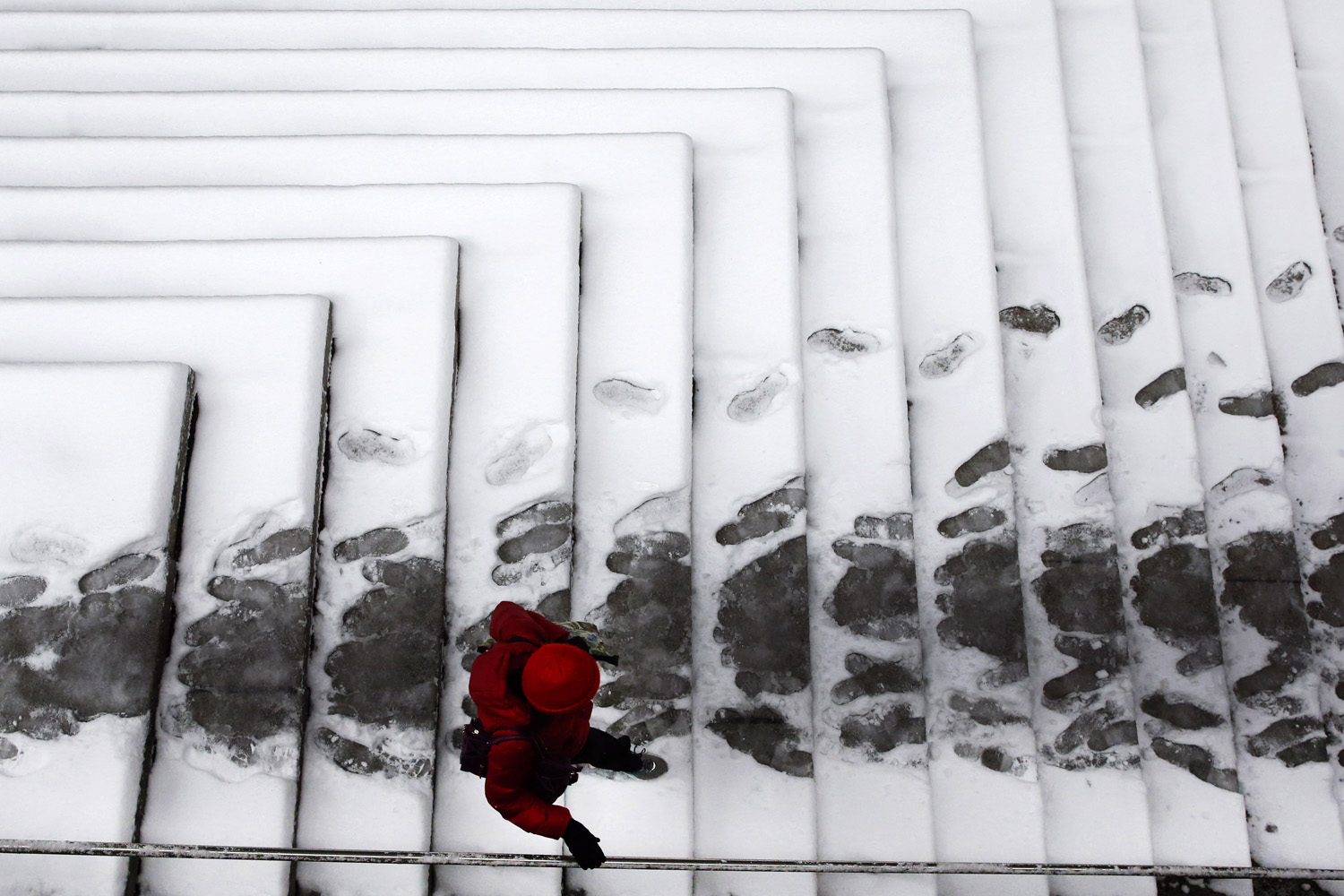 Mar. 17, 2014. A woman makes her way down snow-covered steps outside an office building in Baltimore. Winter-weary commuters faced another treacherous trip Monday in parts of the Mid-Atlantic as snow and frigid weather blew in just days before the start of spring.