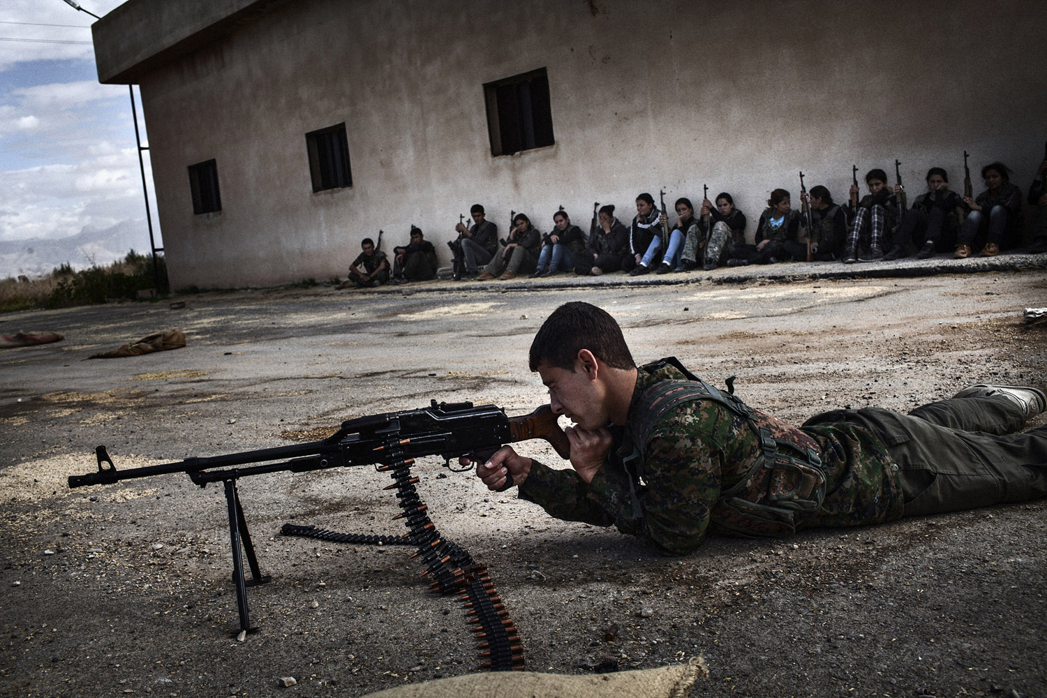 A young Syrian-Kurdish  man practices for shooting during a training session organized by the YPG.