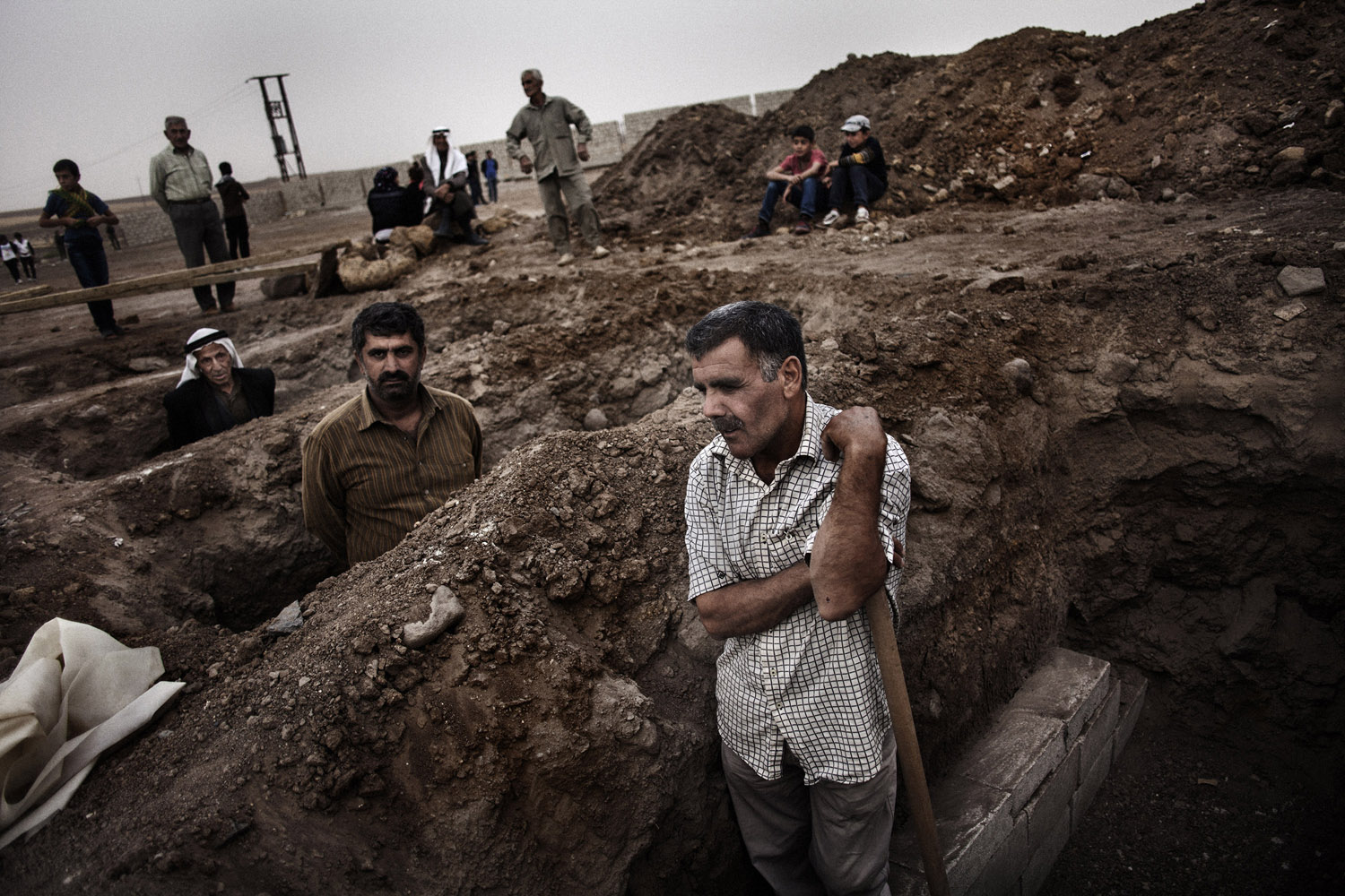Kurdish gravediggers rest after digging the holes that will hold the coffins of soldiers killed during the fighting between YPG, the Nusra Front and ISIS.