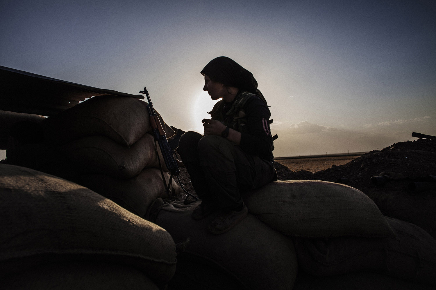 A fighter of YPJ, the women-only Kurdish defense force, sits on sand bags as she holds position on the front line near the Syrian town al-Malikiyah (Derik), in the northeast along the borders with Turkey and Iraq.