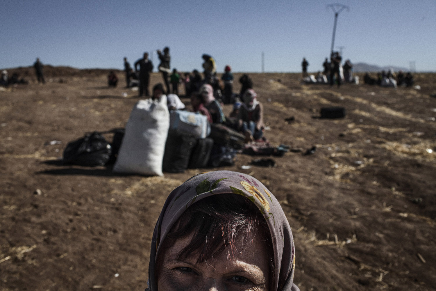 Internally displaced Kurds wait near the Syrian side of the border with Iraq.