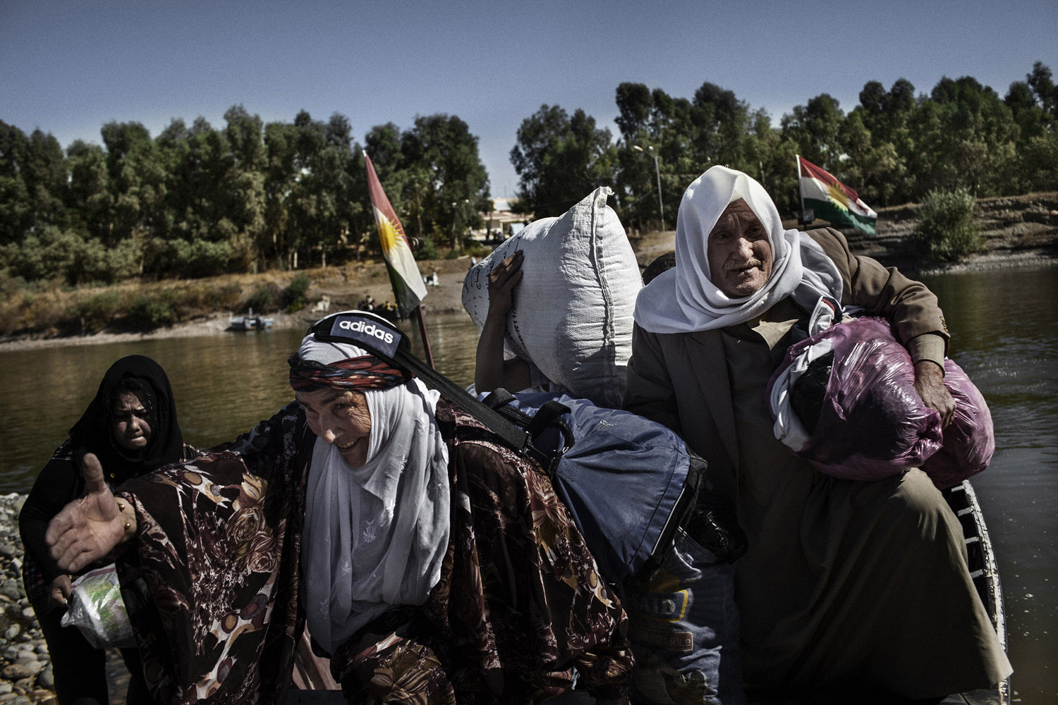 Displaced Syrian Kurds descend from the boat that shuttled them over the Tigris River to Iraq. Several refugees who fled the war in Syria returned to visit their relatives who stay in their native land.
