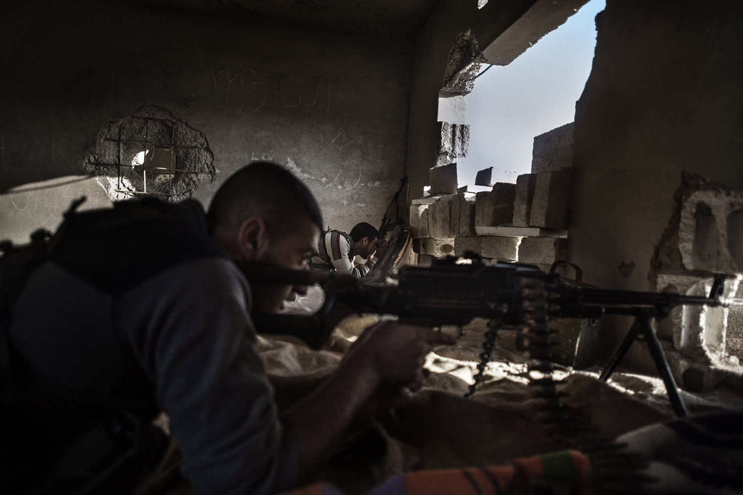 Armed YPG fighters hold position inside a trench in the Syrian town of Ras al-Ain, close to the Turkish border.