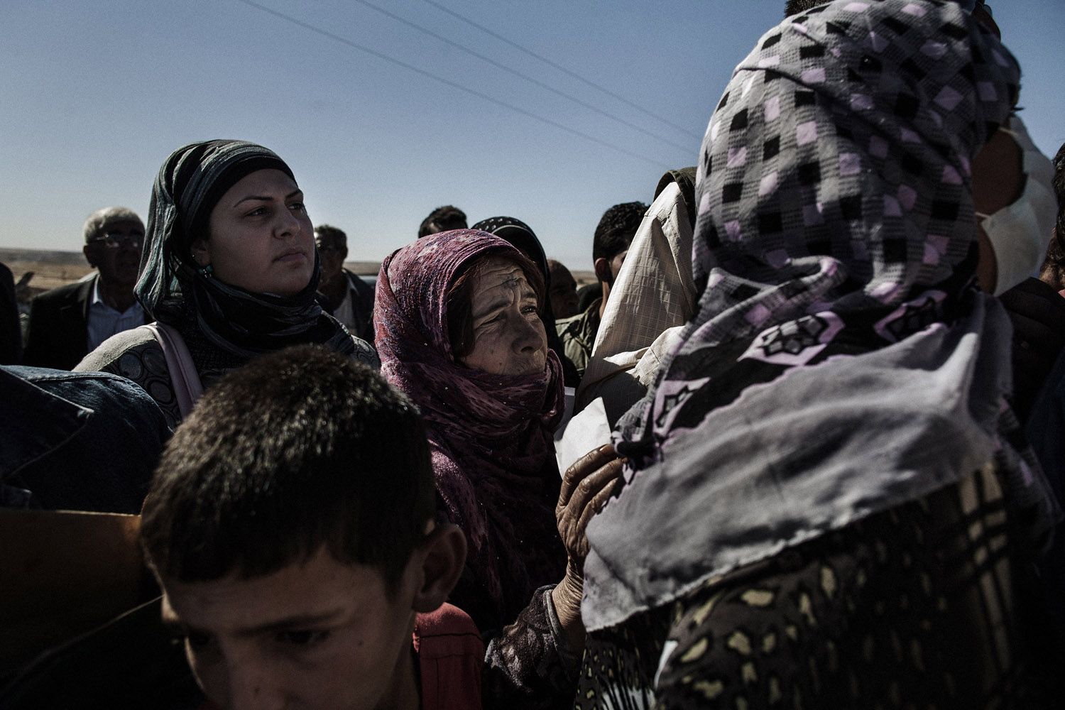 Internally displaced Syrian Kurds wait to receive permission to leave Syria and cross the Tigris River into Iraq.
