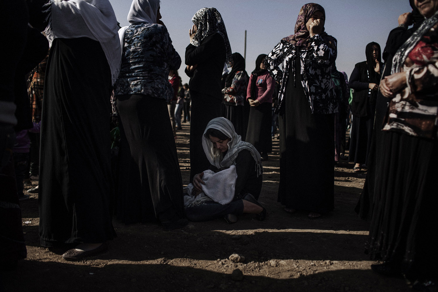 A Kurdish woman with her baby during the celebration to remember their relatives killed in the fights at the martyrs' cemetery near al-Malikiyah (Derik) on the first day of the holiday Eid.