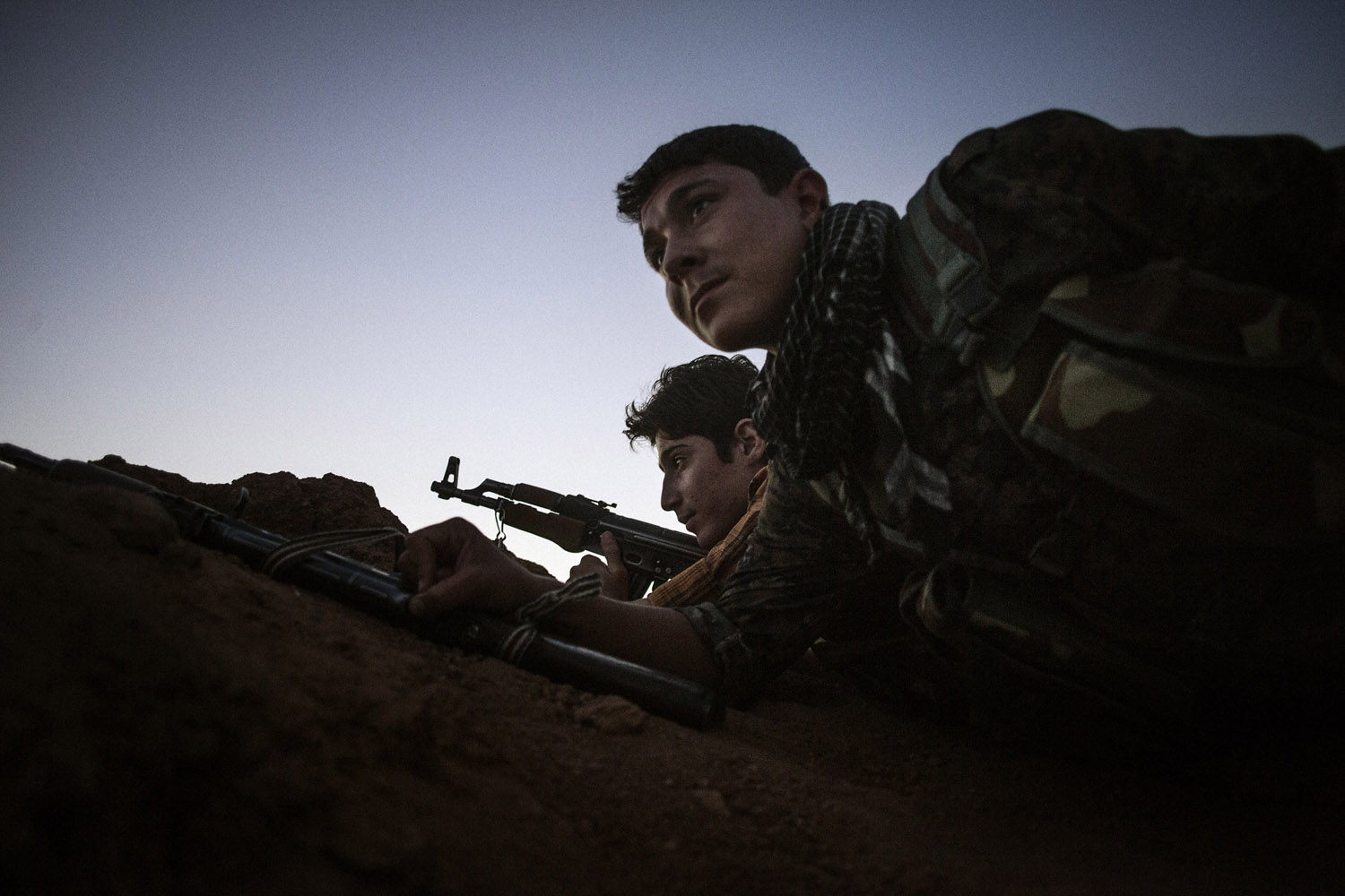 Armed YPG fighters take position inside a trench  in the Syrian town of Ras al-Ain, close to the Turkish border.