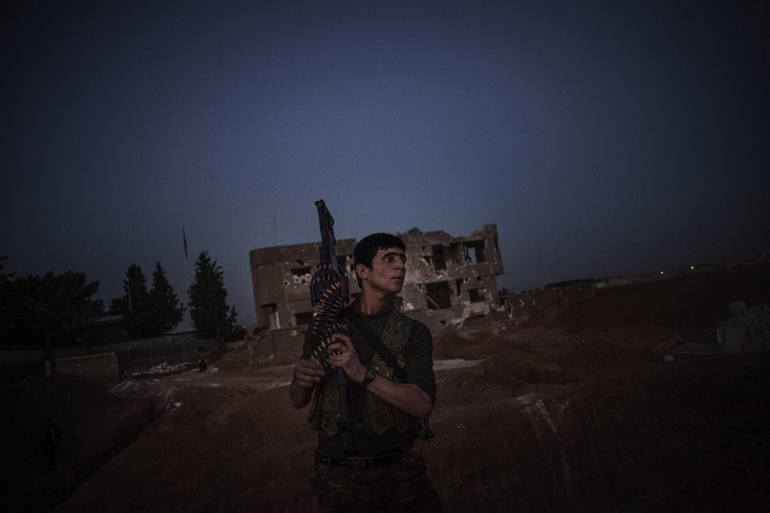 A YPG soldier carries his weapon while heading to his position on the front line in Ras al-Ain, close to the Turkish border.
