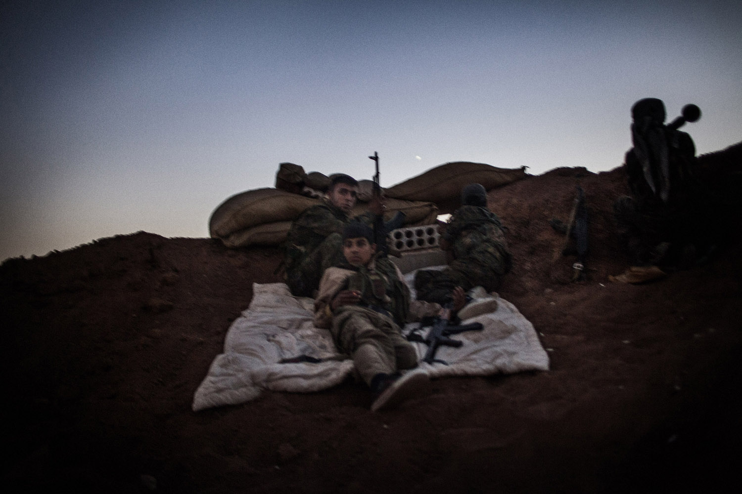 An armed YPG fighter rests while his companion take position behind sand bags inside a trench in the Syrian town of Ras al-Ain, close to the Turkish border.