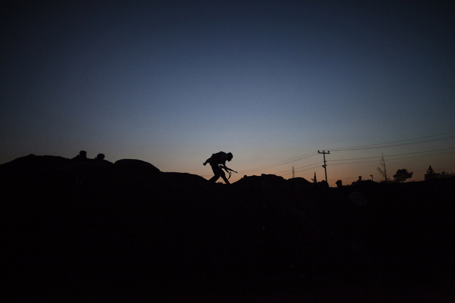 The silhouette of an armed YPG fighter runs to take position along the front line in Ras al-Ain, near the Turkish border.