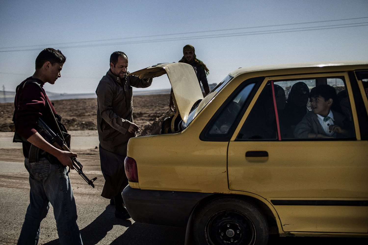 YPG fighters inspect a car at the checkpoint along the road between al-Qamishli and al-Malikiyah (Derik)