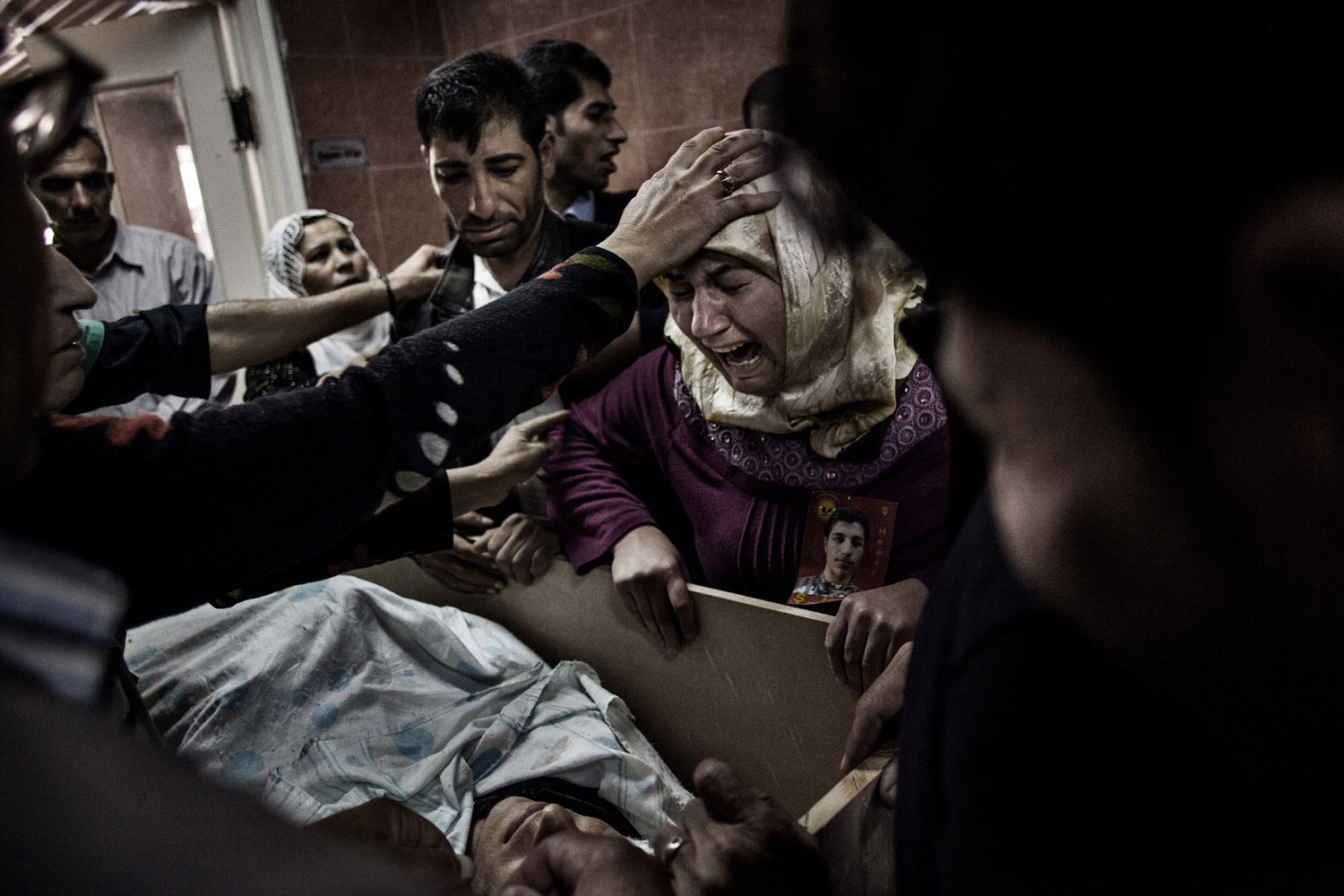 Relatives of a YPG fighter killed in the battles against the Nusra Front, near Ramelan, mourn over his body at the hospital morgue in al-Malikiyah (Derik).