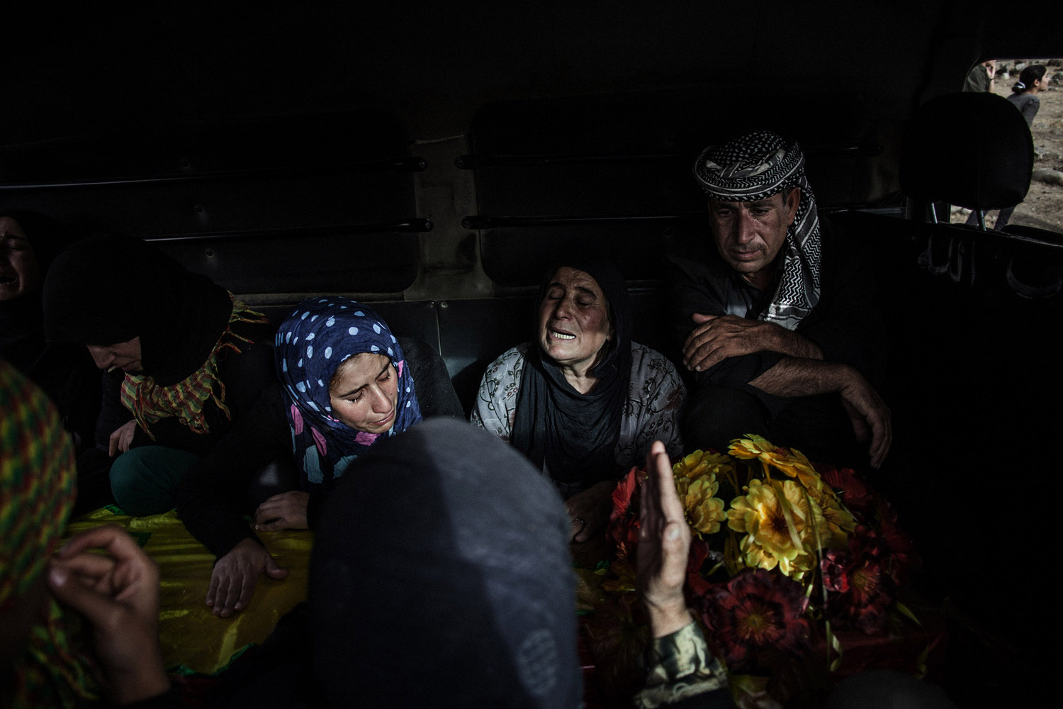 Relatives of a YPG fighter killed in the fighting against the Nusra Front mourn over his coffin in a van in al-Malikiyah (Derik).