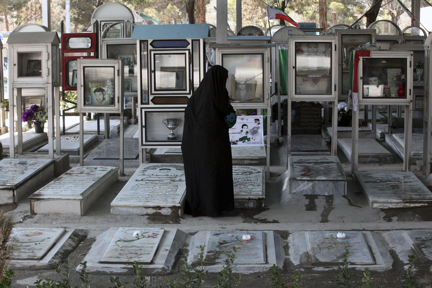 Mar. 20, 2014. An elderly Iranian woman looks at the graves of soldiers who were killed during 1980-88 Iran-Iraq war, at the Behesht-e-Zahra cemetery just outside Tehran, Iran.