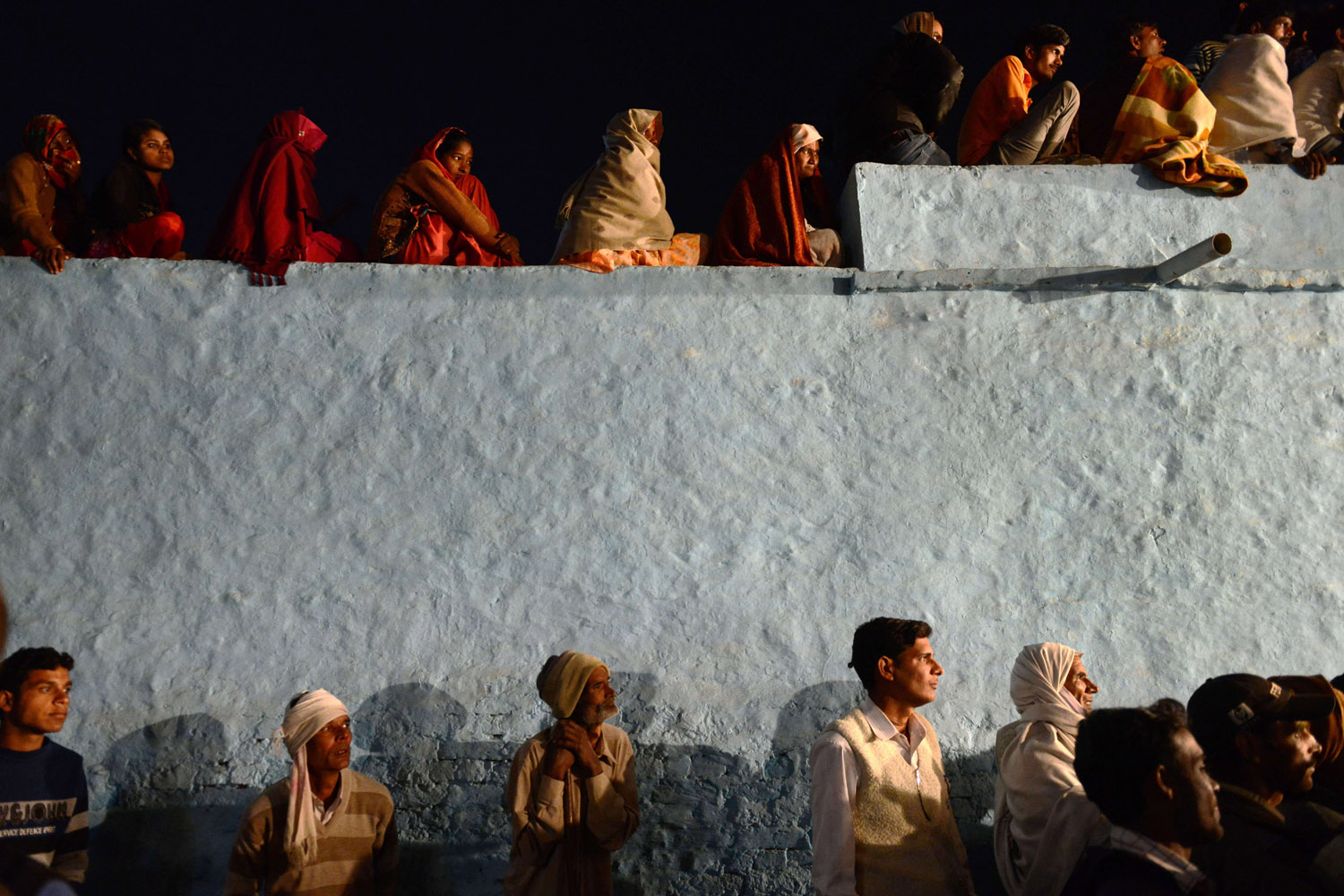 Mar. 17, 2014. Indian revelers gather on a rooftop to watch a performance of a local folk drama during a ritual to mark the first day of the Holi spring festival, also known as the Festival of Colors.