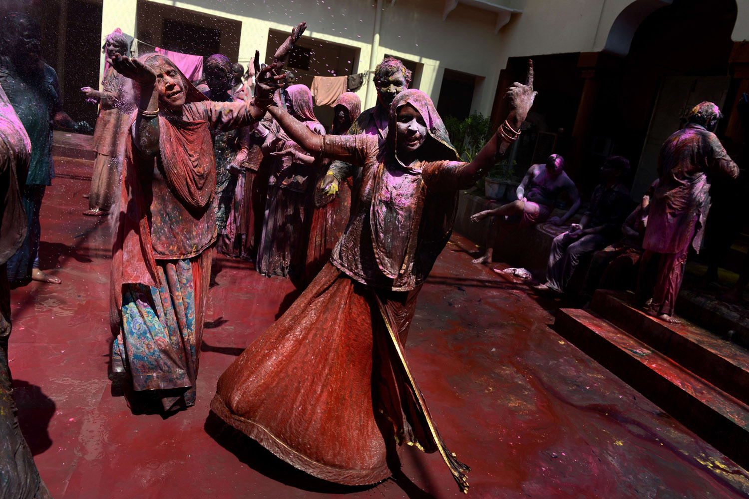 Mar. 17, 2014. Indian devotees covered in colored powder dance during Holi celebrations in Vrindavan. Holi, also called the Festival of Colors, is a popular Hindu spring festival observed in India at the end of the winter season on the last full moon of the lunar month.