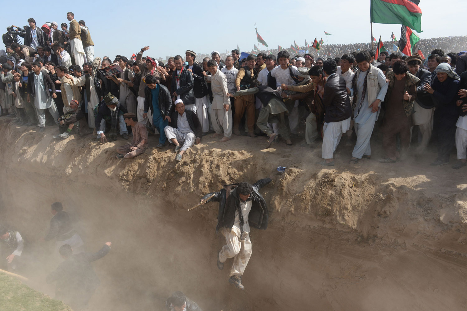 Mar. 19, 2014. Supporters of Afghan presidential candidate Ashraf Ghani jump to cross a ditch after a gathering in the outskirts of Kunduz province, north of Kabul.