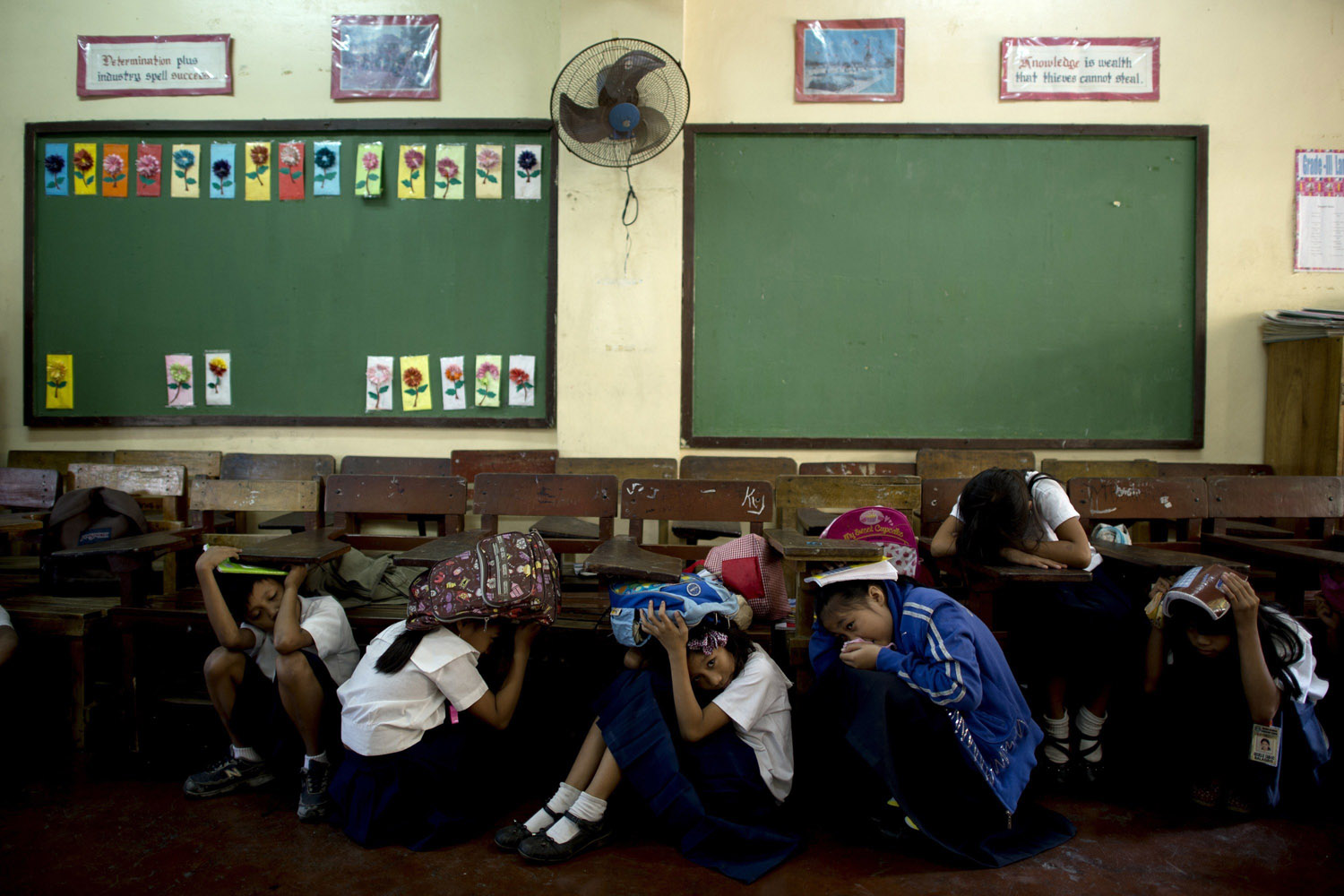 Mar. 19, 2014.                                Students of Bagong Silangan Elementary school cover their head during an earthquake drill in Manila. The students participated in a national emergency earthquake drill that aims to generate awareness on disaster risk reduction and assess their capacity level to respond during a disaster.