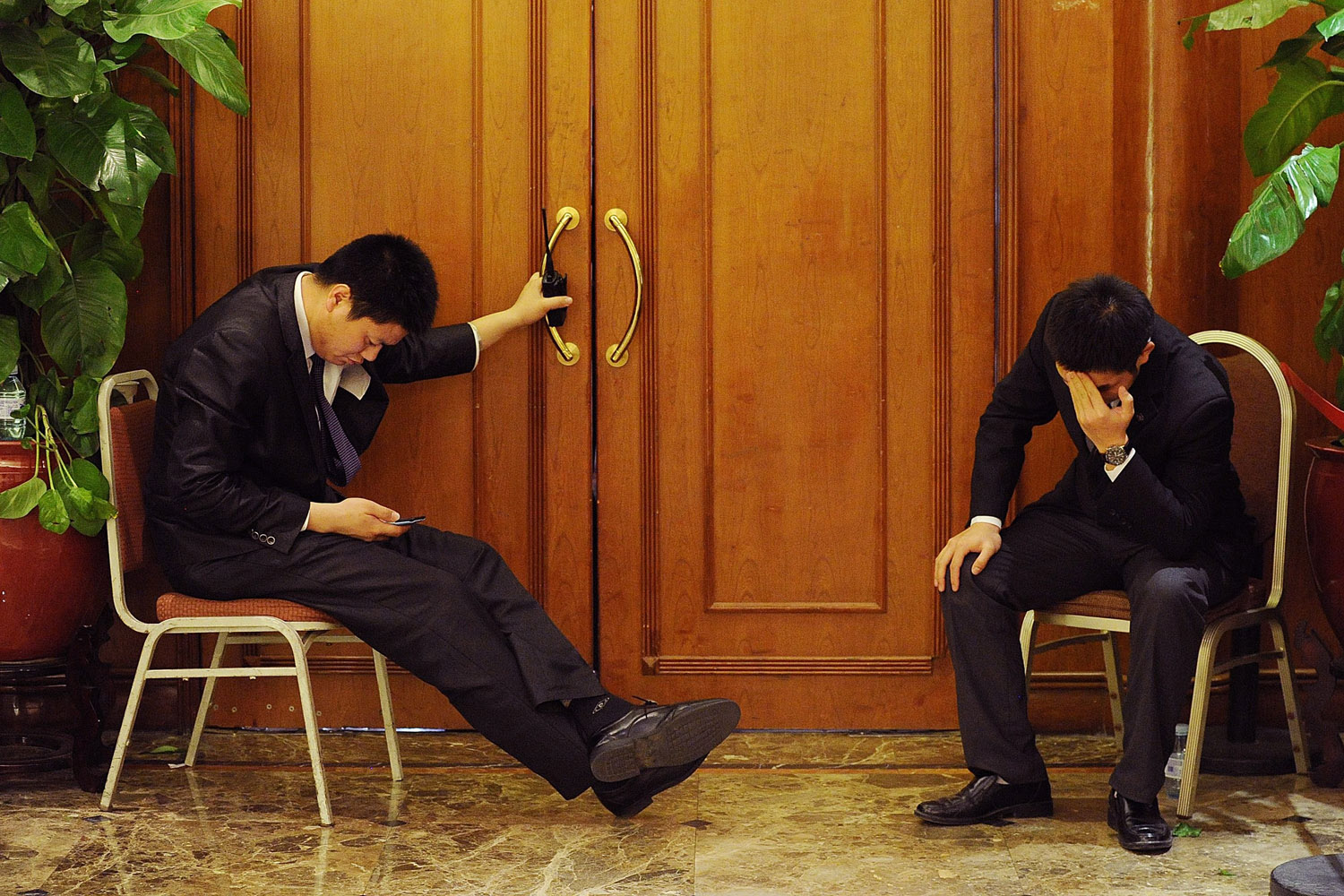 Mar. 19, 2014.                               Two security officers sit at the entrance of a hotel lounge where relatives of passengers from the missing Malaysia Airlines flight MH370 are gathered in Beijing. Tempers flared among Chinese relatives of passengers aboard the missing flight.