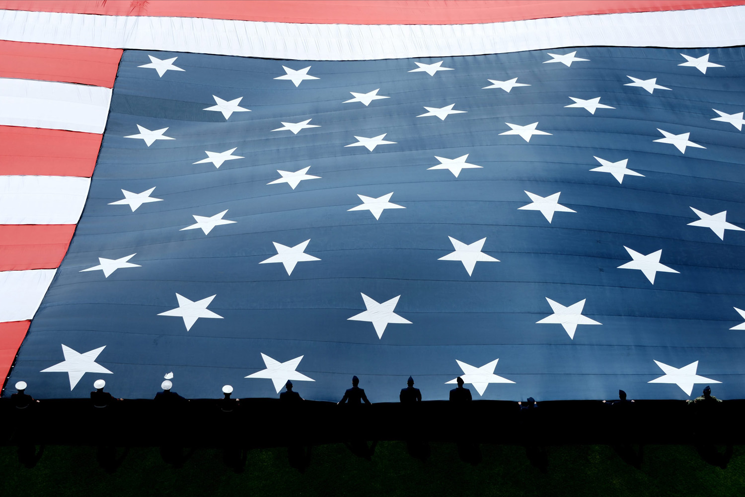 Mar. 31, 2014. A giant American flag is unfurled on the field during ceremonies before the start of the game between the Washington Nationals and the New York Mets at Citi Field in Flushing Meadows, New York.