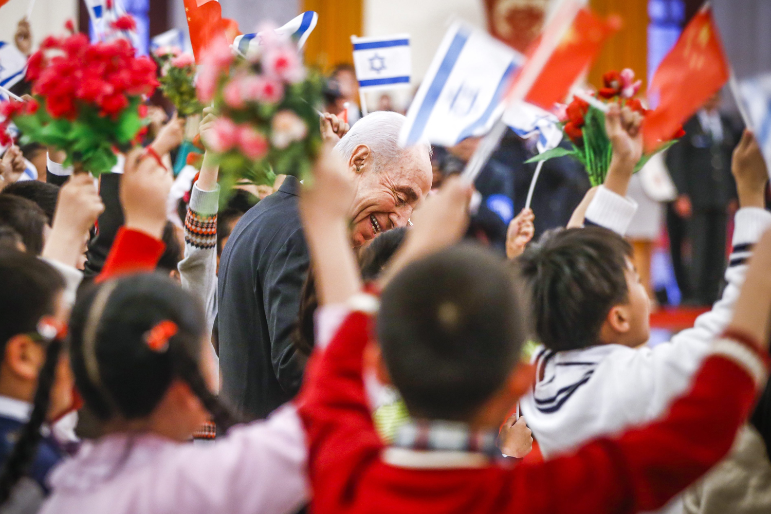 Apr. 8, 2014. Israeli President Shimon Peres (C) talks to school children holding Chinese and Israeli national flags during a welcoming ceremony hosted by Chinese President Xi Jinping (not in picture) inside the Great Hall of the People in Beijing, China.