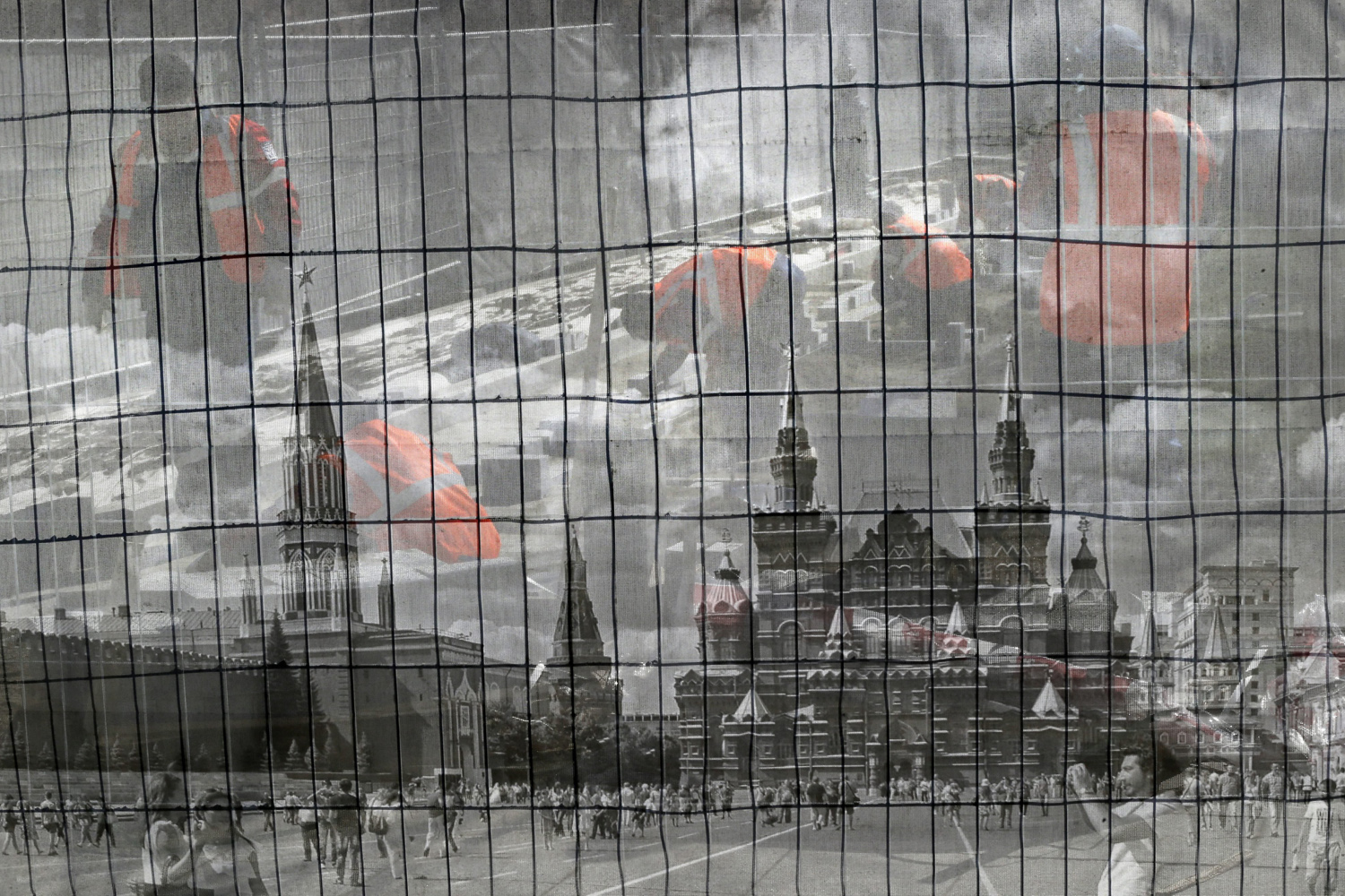 Apr. 10, 2014. Municipal workers from Asian republics are seen through a fence with pictures of the Red Square during their work on landscaping around the Kremlin in Moscow, Russia.