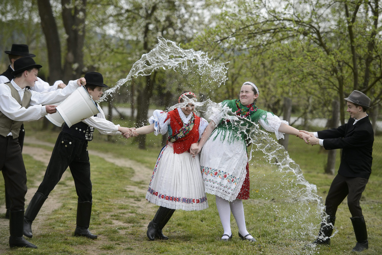 Young men dressed in traditional Paloc folk costumes pour water from buckets on two young women performing an Easter folk tradition for the Easter sprinkling in Kazar, some 100 km northeast of Budapest, Hungary, April 18, 2014.