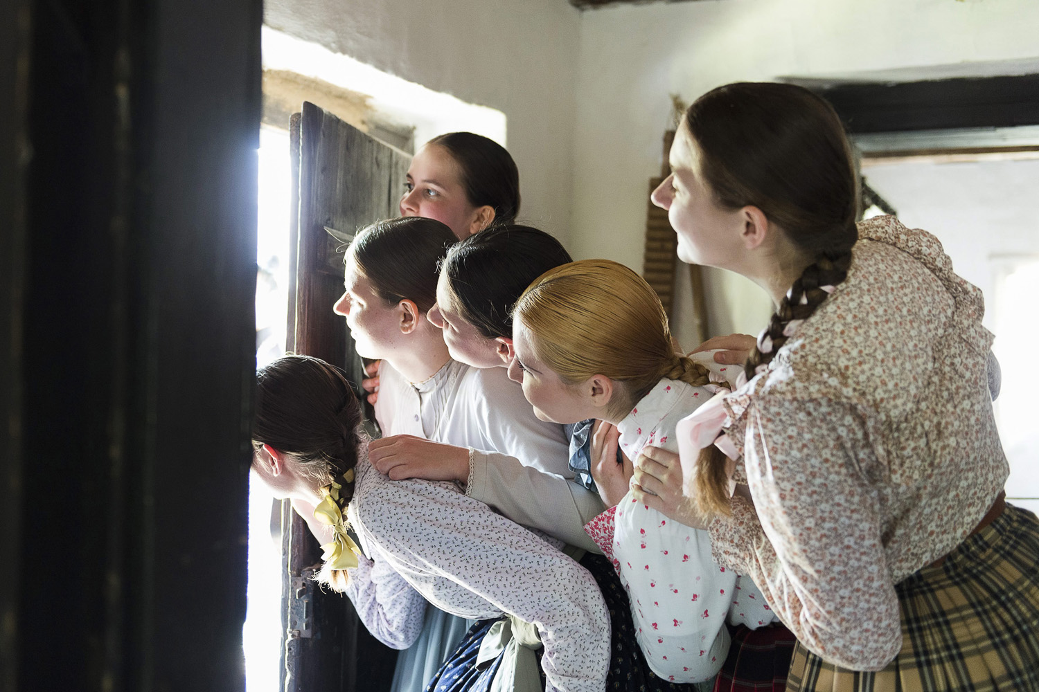 Dressed in folk costumes, young women peer out from a house waiting for male visitors amid performances of local Easter folk traditions at the Open Air Village Museum in Nyiregyhaza, northeast of Budapest, Hungary, April 21, 2014.