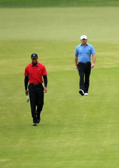 Tiger Woods and Graeme McDowell of Northern Ireland walk down the fourth fairway during the final round of the Chevron World Challenge at Sherwood Country Club on Dec. 5, 2010 in Thousand Oaks, Calif.