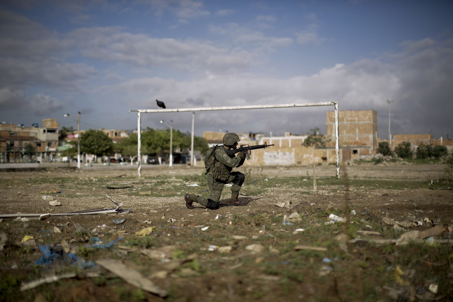 Apr. 5, 2014. A navy soldier patrols on a soccer field during an operation to occupy the Mare slum complex in Rio de Janeiro, Brazil. More than 2,000 Brazilian Army soldiers moved into the Mare slum complex early Saturday in a bid to improve security and drive out the heavily armed drug gangs that have ruled the sprawling slum for decades.