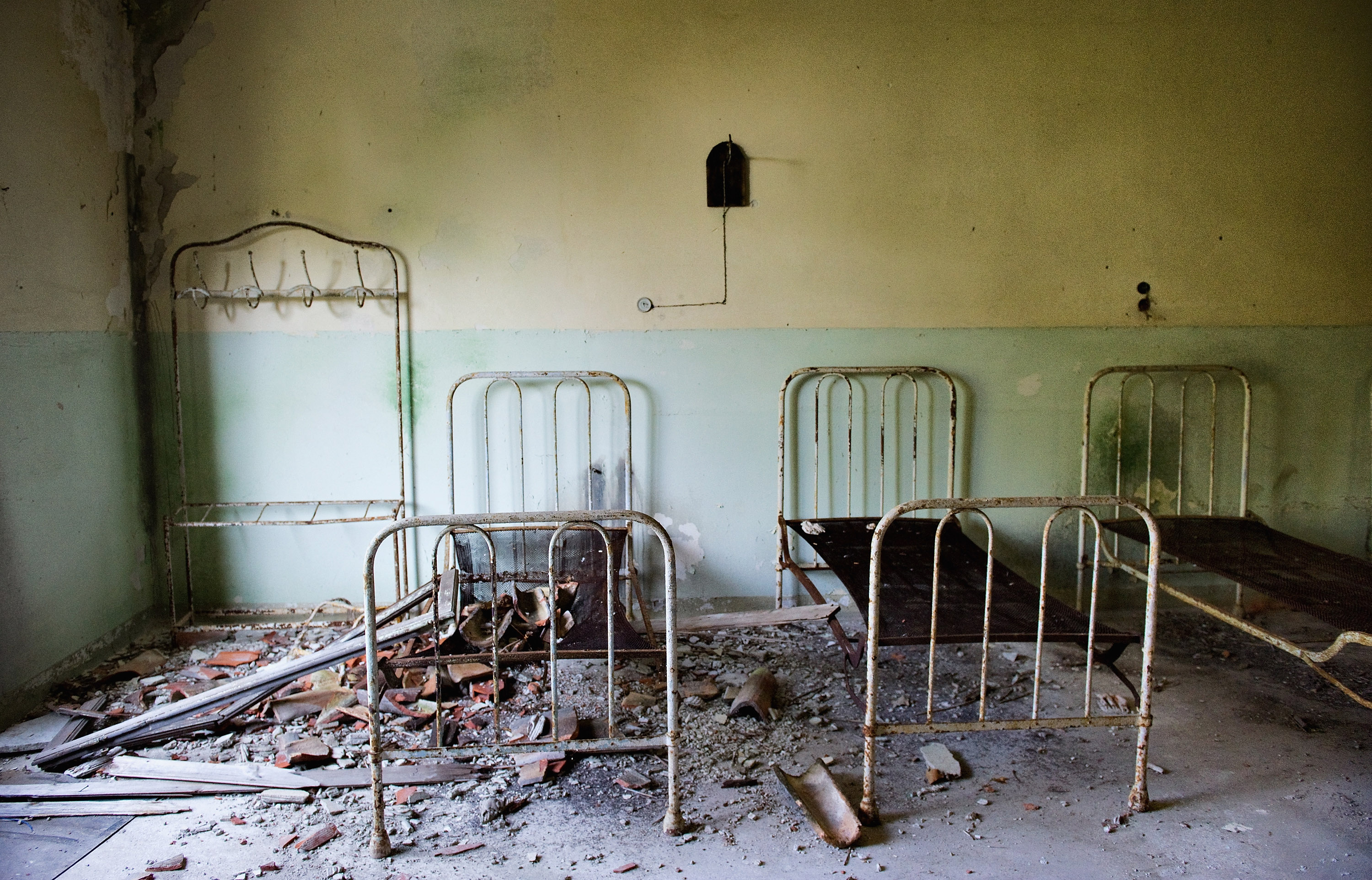 VENICE, ITALY - AUGUST 27:   Beds and furniture remain in one of the dormitories in the psychiatric ward of the abandoned Hospital of Poveglia on August 27, 2011 in Venice, Italy. The island of Poveglia, with its ruined hospital and plague burial grounds, is said to be the most haunted location in the world. The area is located within a multi-million dollar piece of real estate but is deserted and off limits to the public. The dark and derelict forbidding shores are only minutes away from the glamour of the Venice Film Festival on the Lido.  (Photo by Marco Secchi/Getty Images)