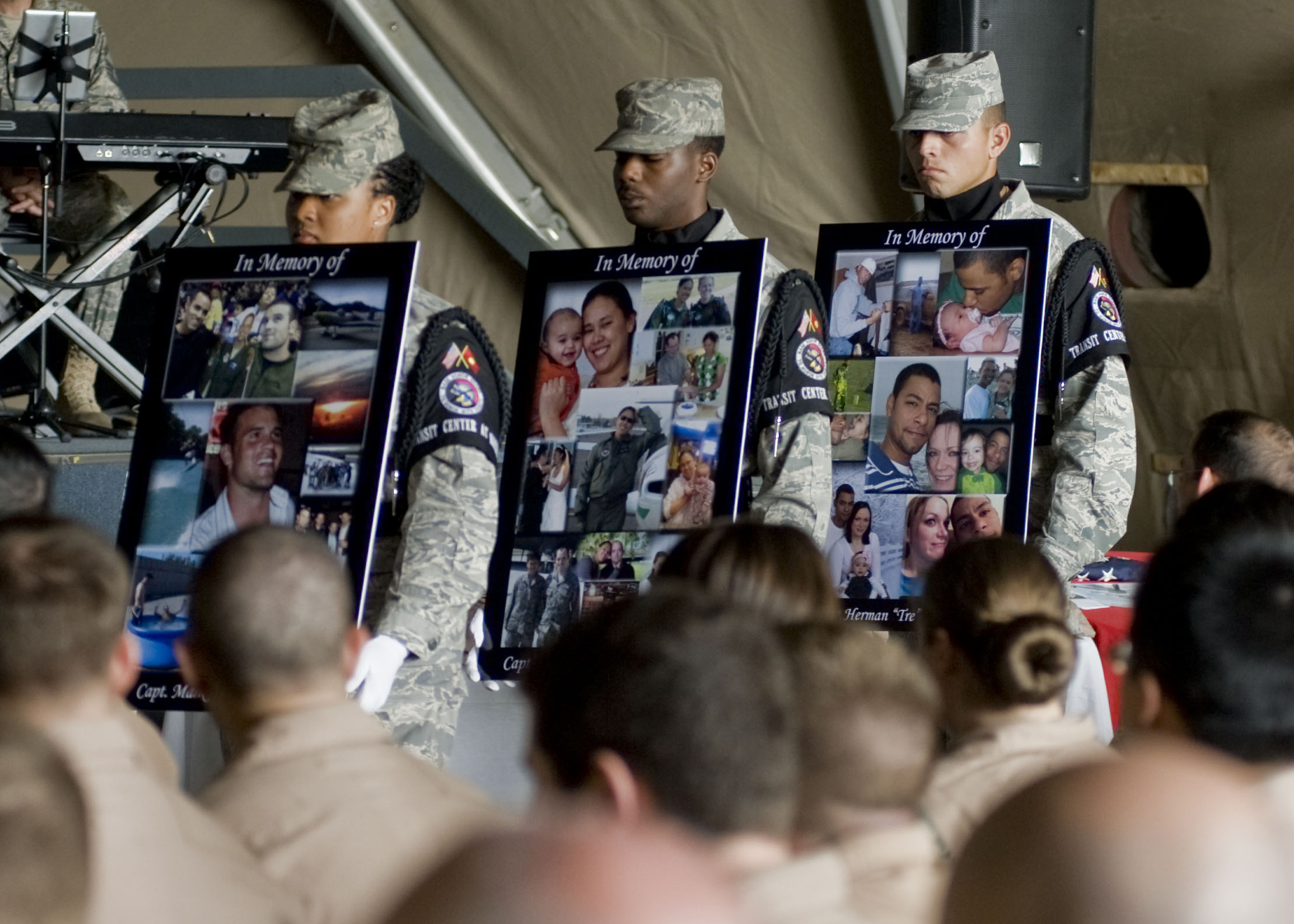 An honor guard carries photos of the KC-135 crew members during a memorial service at Manas six days after the crash.
