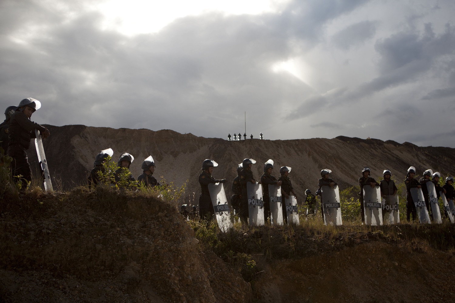 Apr. 28, 2014. Riot police stand guard at an illegal mining operation in Huepetuhe district in Peru's Madre de Dios region in Peru.