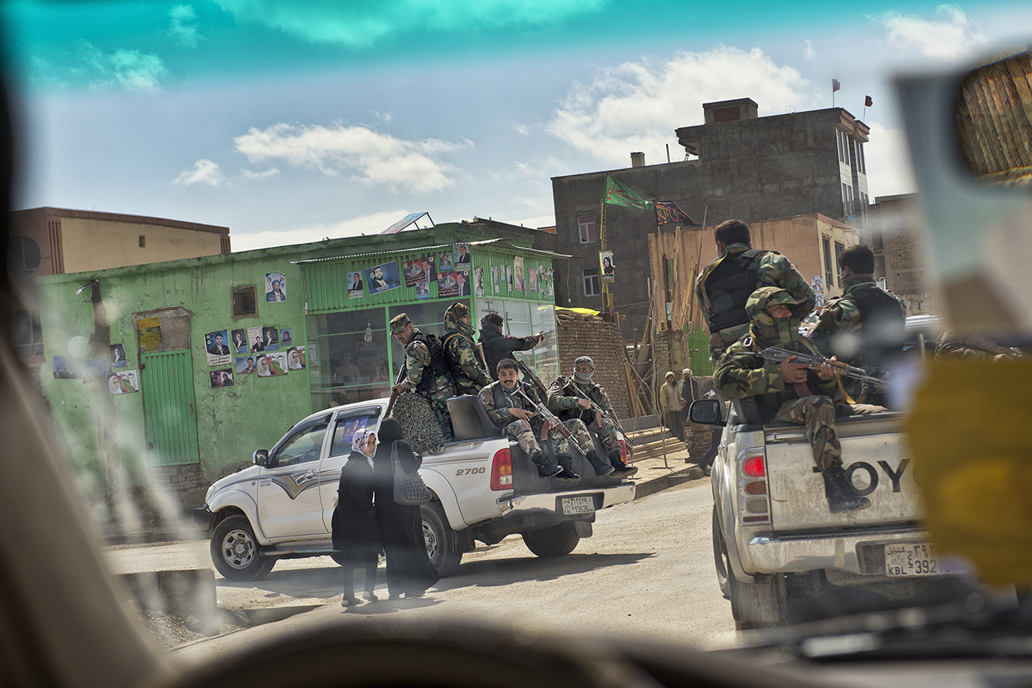 Afghan security forces accompanying Presidential candidate Zalmai Rassoul and Vice Presidential candidate Habiba Sarabi ride past Afghan women in Mazar-i-Sharif, Afghanistan, March 27, 2014.