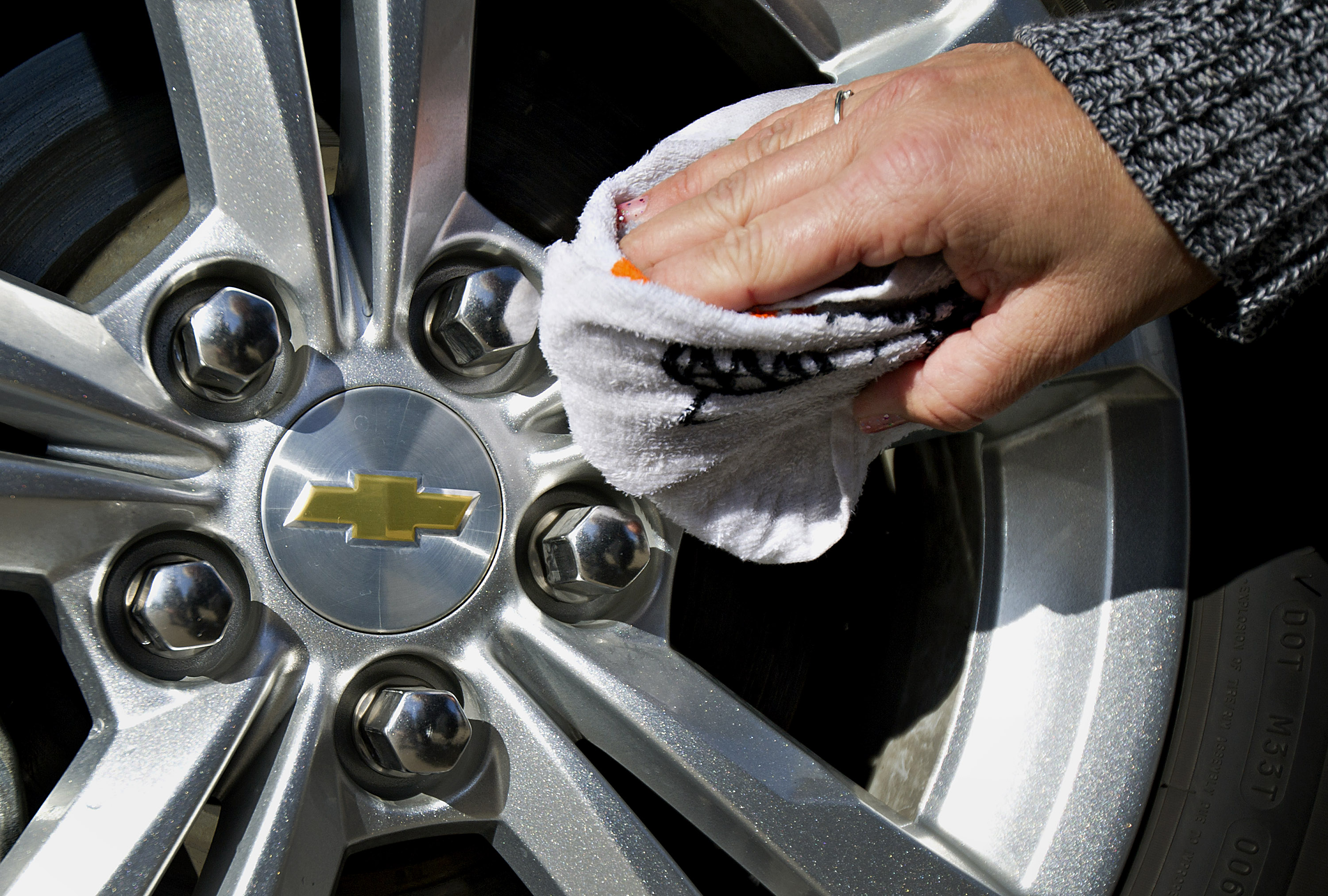 Customer Tracy Boehm wipes the wheel of her 2013 Chevy Equinox