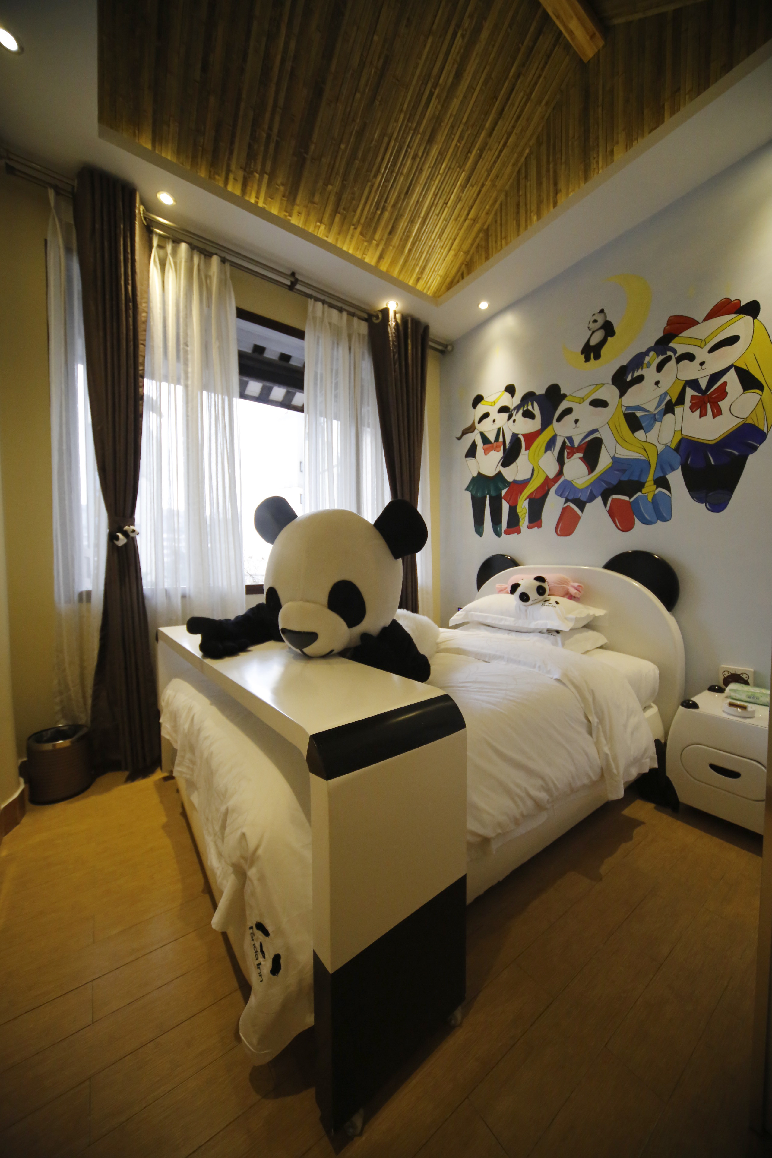 A panda toy on a bed in a room of a panda-themed hotel