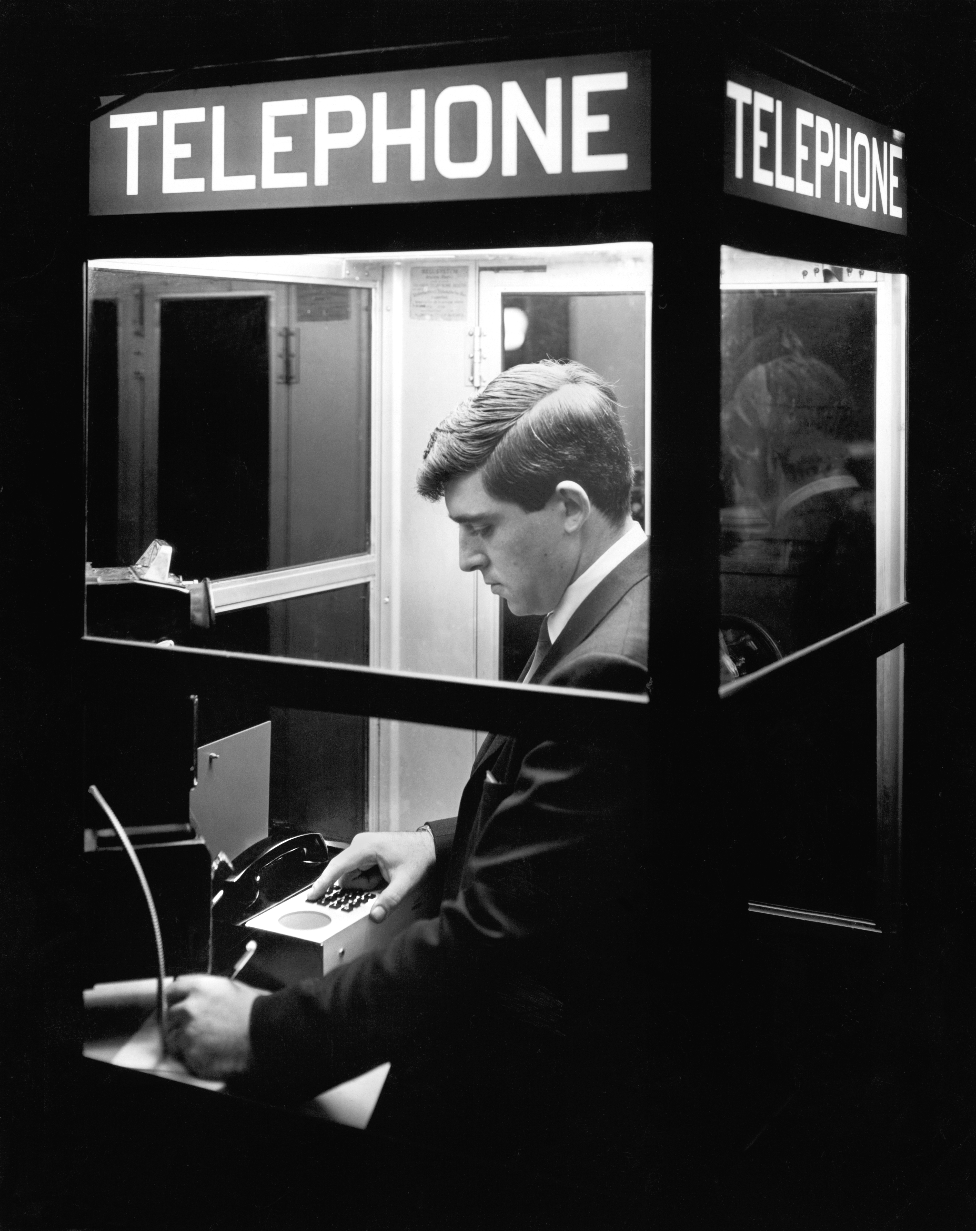 In 1968's version of mobile computing, a man uses a Honeywell portable terminal in a telephone booth