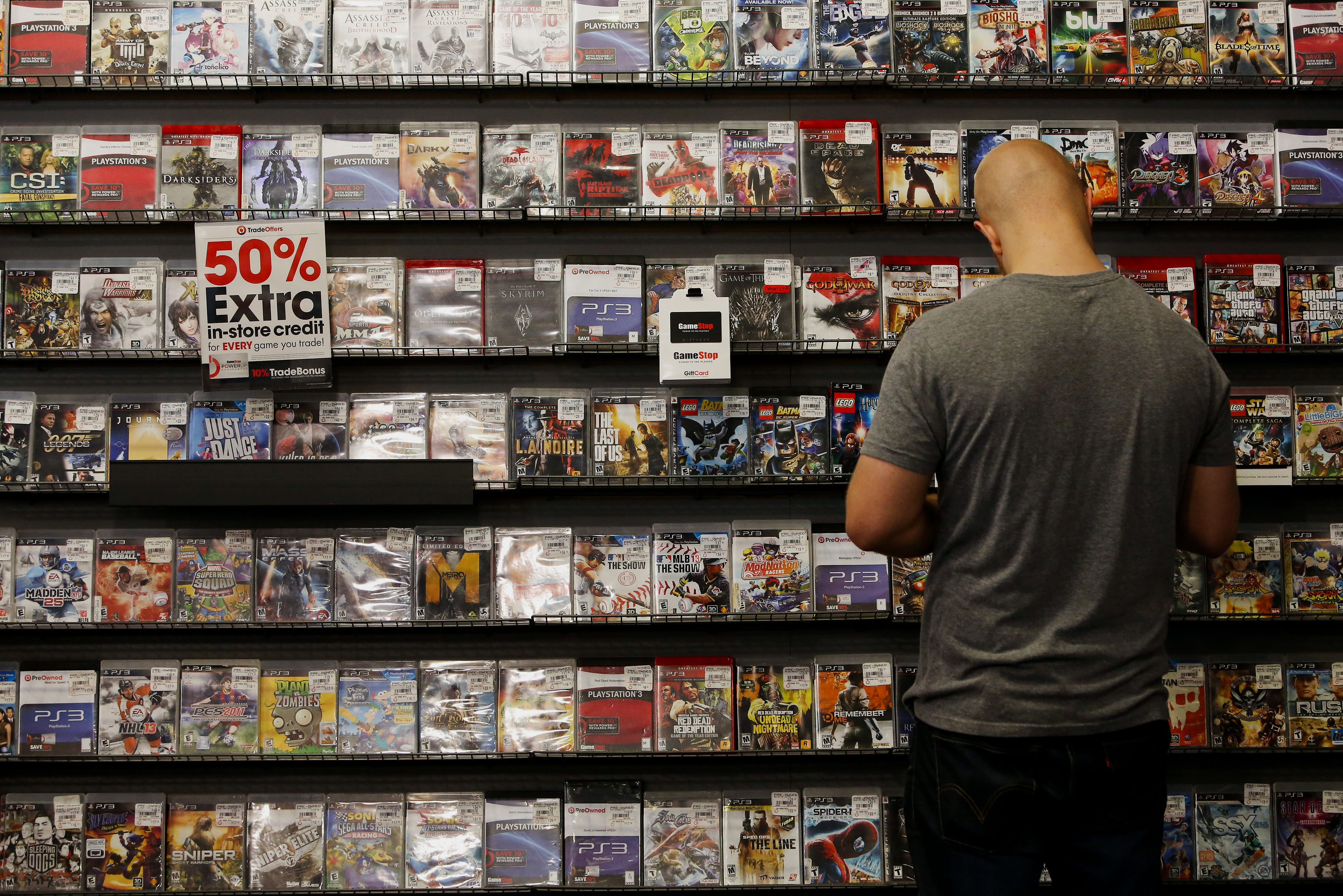 A customer browses a wall of used video games for sale from Electronic Arts and other video game publishers at a GameStop store in West Hollywood, Calif., Oct. 28, 2013.