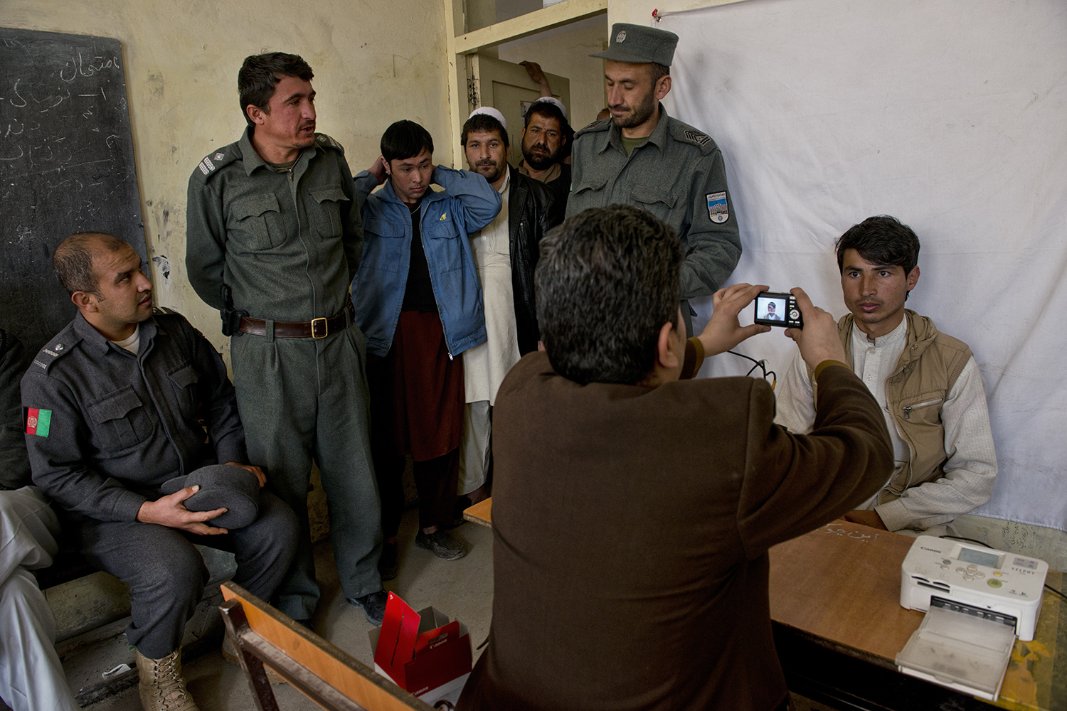 Afghan men make photo IDs for voter registration at a center run by the Afghan Independent Electoral Commission (IEC) in Shah Shaheed, Kabul, Afghanistan, March 25, 2014.