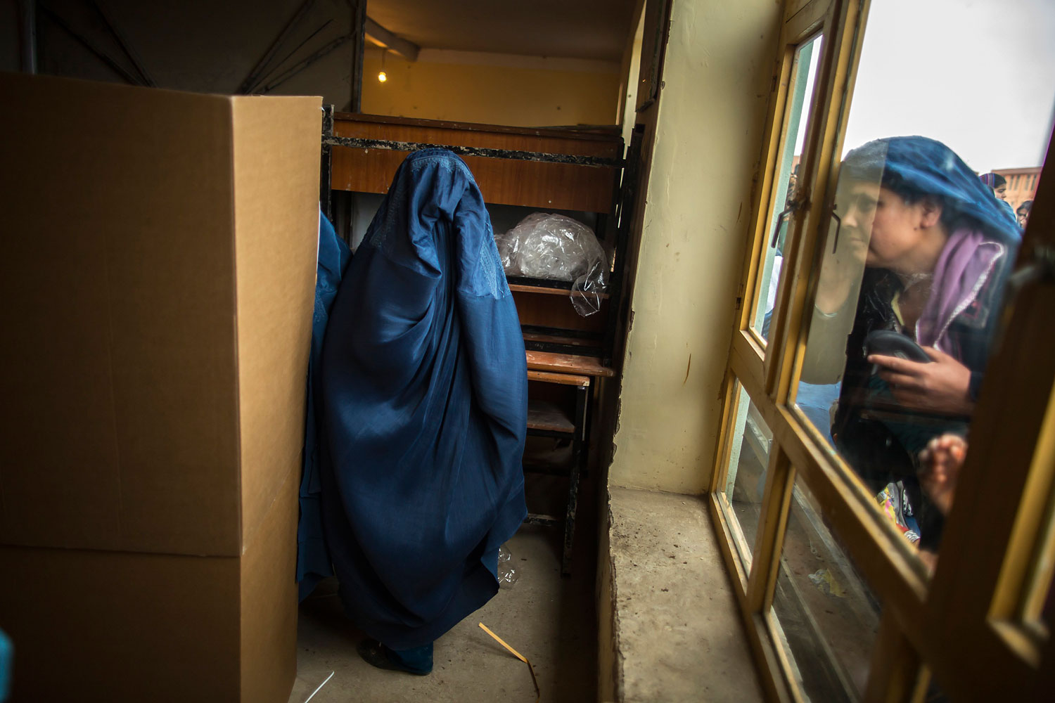 An Afghan woman looks through a window as another is about to cast her ballot.
