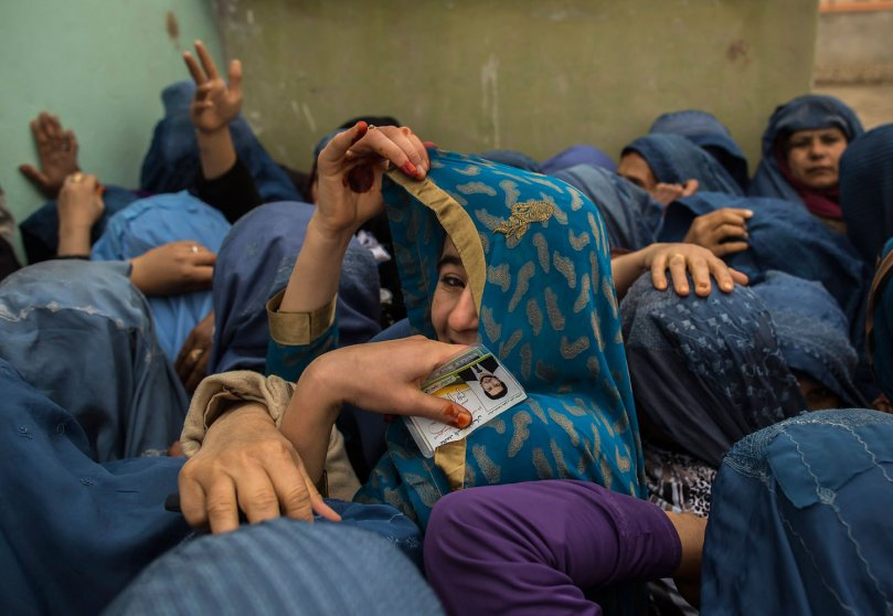 Afghan women wait to cast their ballots at a polling station in Mazar-i-sharif