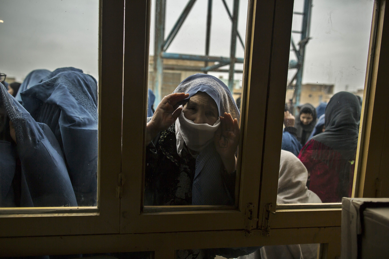 Apr. 5, 2014. An Afghan woman looks through a window as she waits for her turn to vote at a polling station in Mazar-i-sharif. Voting was peaceful during the first few hours of Afghanistan's presidential election on Saturday, with only isolated attacks on polling stations as the country embarked on the first democratic transfer of power since the fall of a Taliban regime in 2001.