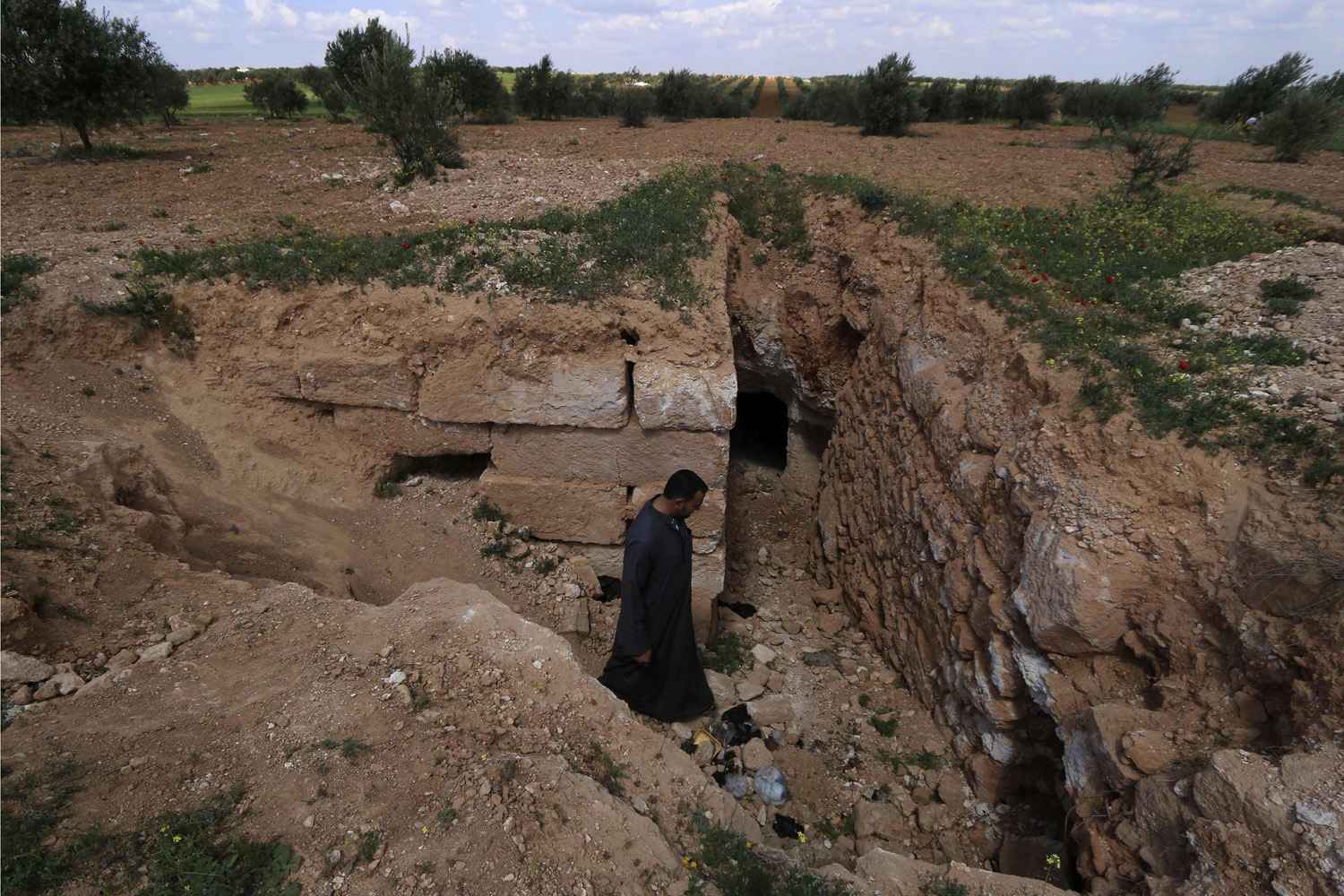 Apr. 9, 2014. A man enters an underground shelter in Idlib countryside. Residents dug underground shelters to hide in during shelling from forces loyal to President Bashar al-Assad.