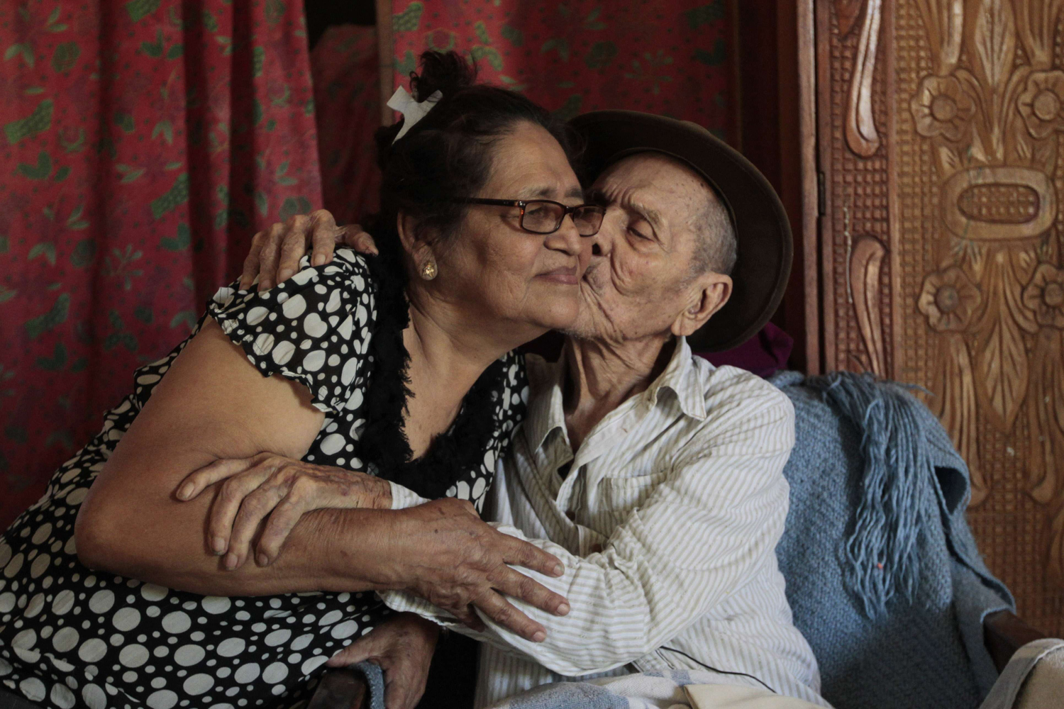 Apr. 8, 2014. Hector Gaitan, 110, kisses his wife Nora Campo inside his home, at an abandoned station of the Nicaraguan Railway Company, the country's defunct railway, located on the outskirts of Managua.