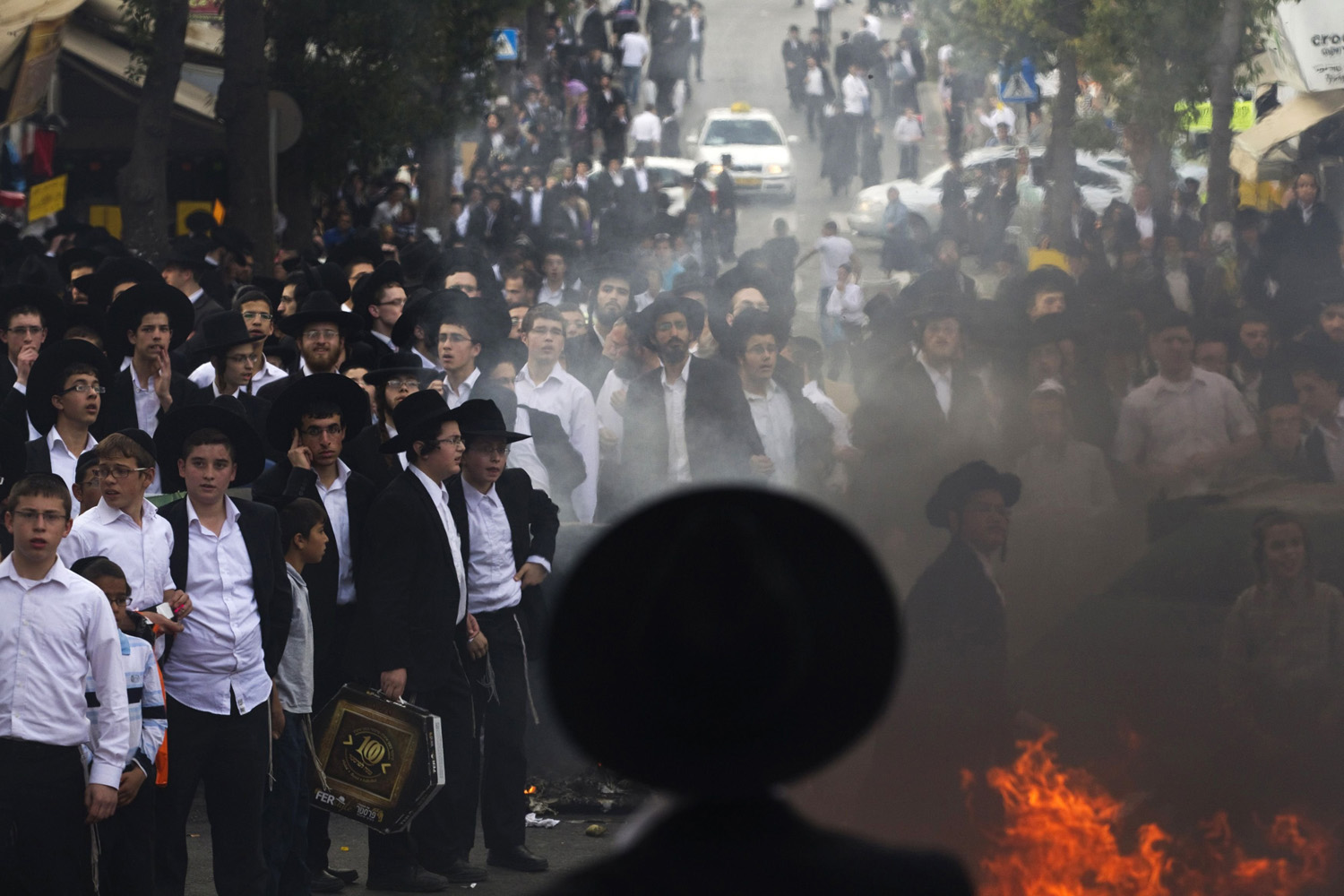 Apr. 10, 2014. Ultra-Orthodox Jewish men and youths stand next to a fire during a protest in Jerusalem's Mea Shearim neighbourhood. Hundreds of ultra-Orthodox Jewish men protested on Thursday against the jailing of a Jewish seminary student who failed to comply with a recruitment order.